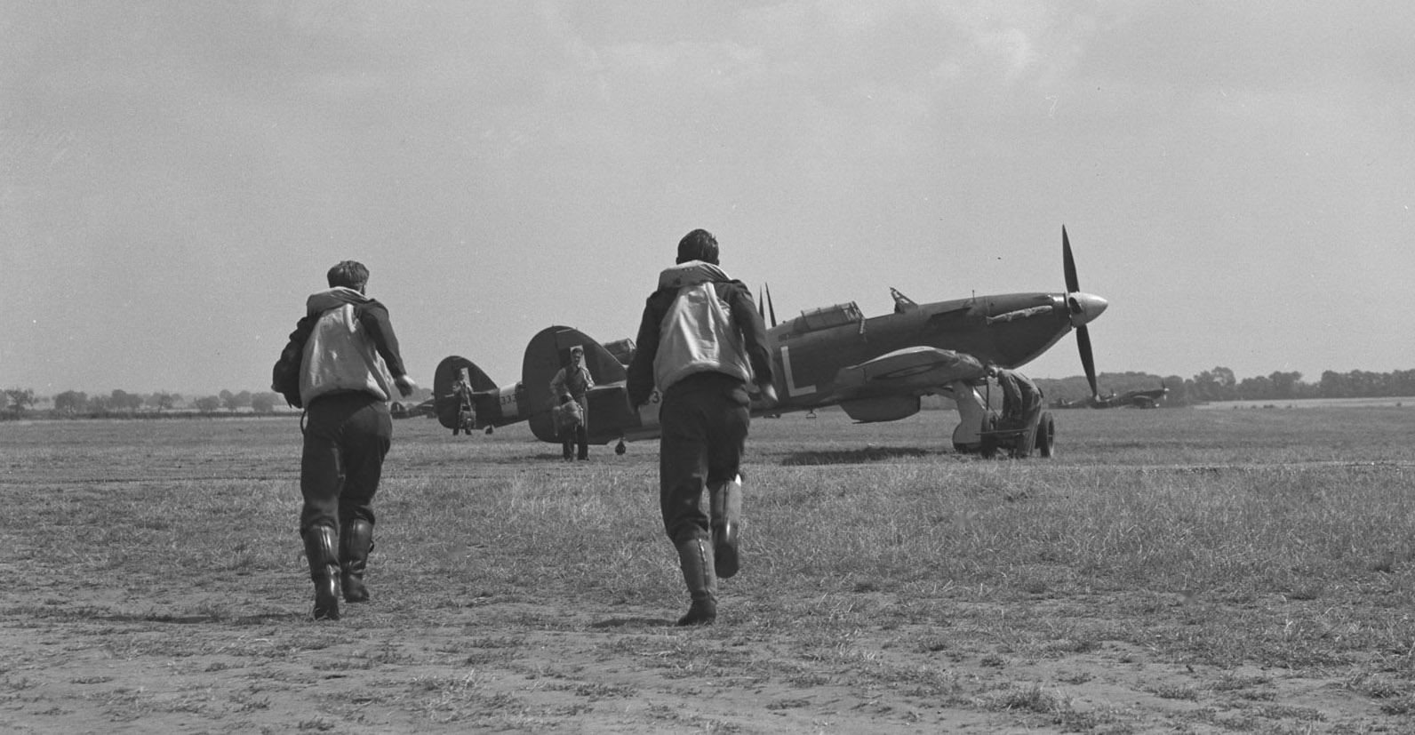 Pilots from 401 Squadron run to their Hurricane aircraft in this undated photograph. Groundcrew are waiting to help the pilots put on their parachutes and get into the aircraft. The Hurricanes could skim off the ground three minutes after an alarm was sounded. PHOTO: DND Archives, PL-4484