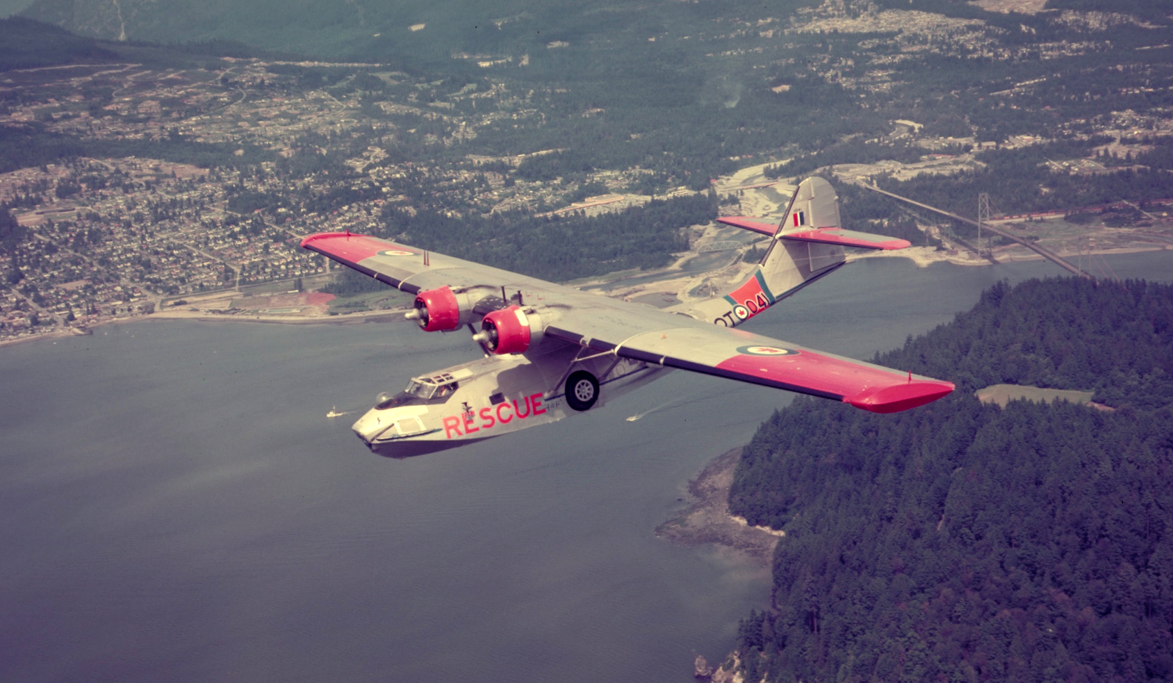 A Canso painted in search and rescue colours flies over the Lions Gate Bridge in British Columbia. PHOTO: DND Archives, PC-2156