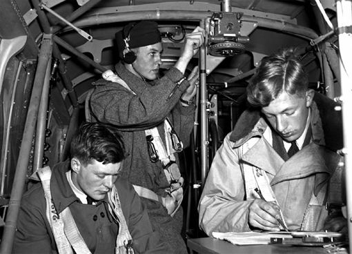 On June 4, 1941, RCAF Sergeant E. Romilly, the Royal Australian Air Force's W. Betts, and the Royal Air Force's J. Mahoud practise navigation techniques on board an Anson aircraft at No. 1 Air Navigation School, RCAF Rivers, Manitoba. PHOTO: DND Archives