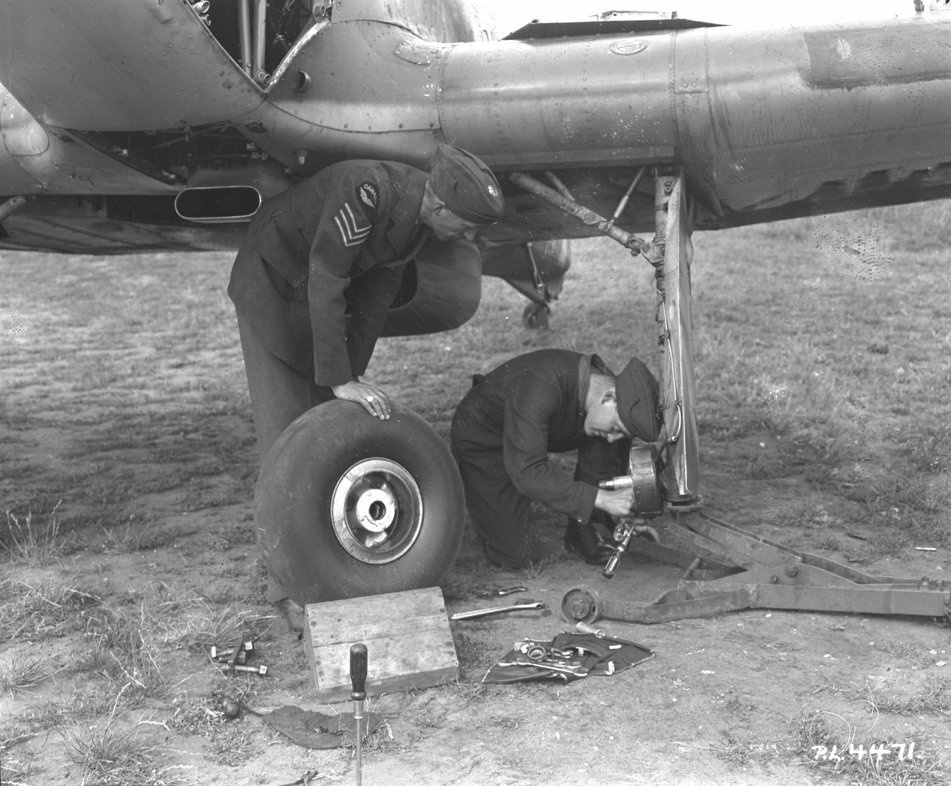 Members of No. 1 Squadron's ground crew tend to a Hurricane. While Leading Aircraftman P.J.  Thurgeon removes the port wheel from a Hurricane because of faulty brakes, Sergeant Bob Fair checks to see if the craft should go into maintenance to be repaired. Often forgotten, No.1's ground crew worked tirelessly to keep the aircraft in good repair; without them the squadron could not have flown. PHOTO: Library and Archives of Canada, PL-4471