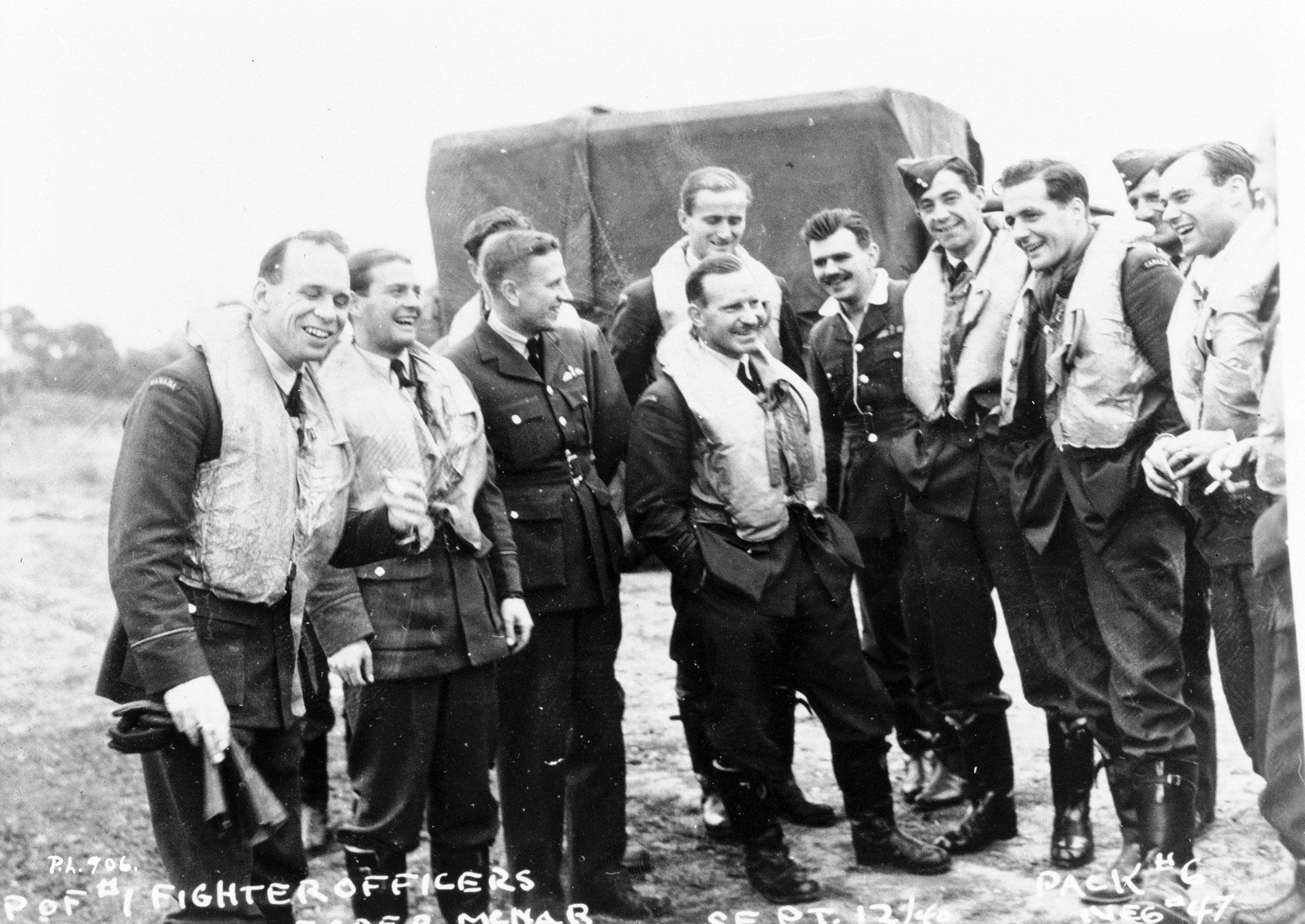 Squadron Leader Ernest McNab and some of his pilots pose for a photo and a laugh September 12, 1940, during the Battle of Britain: (left to right) Flying Officer William P. Sprenger, Flying Officer Otto John Peterson, Flight Lieutenant W.R. Pollock (adjudant), Flying Officer Paul Brooks Pitcher, Squadron Leader McNab, Flying Officer Peter William Lochnan, Flight Lieutenant Edwin Michael Reyno, Flying Officer Eric Walter Beardmore, Flying Officer S.T. Blaiklock (intelligence officer) and Flying Officer Robert William Norris. PHOTO: Library and Archives of Canada, PL-906