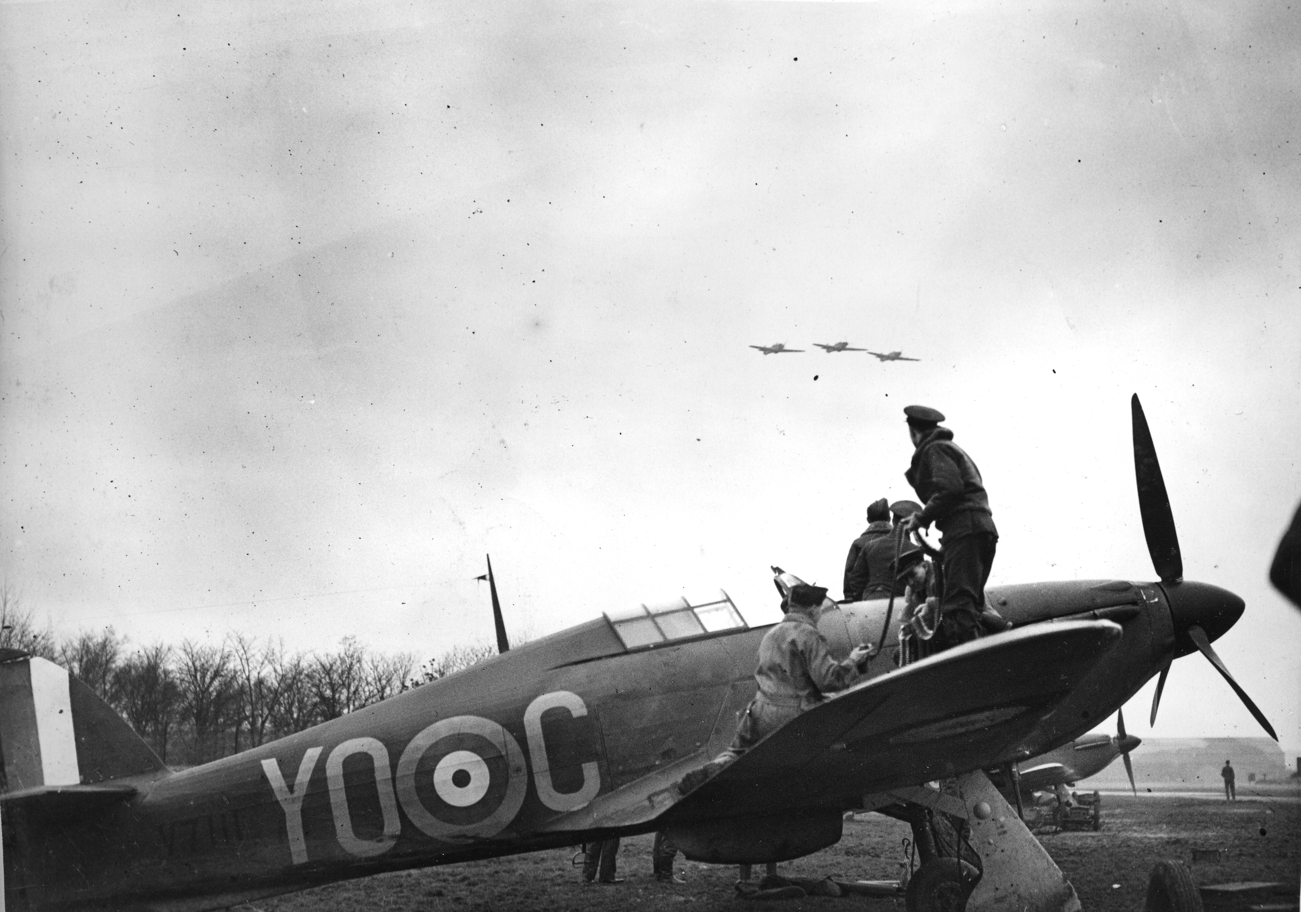 A Hurricane is re-armed while a section flies overhead. From the photo album of Flying Officer R.W.G. Norris, from Saskatoon, Saskatchewan, who served with No. 1 Squadron during the Battle of Britain.