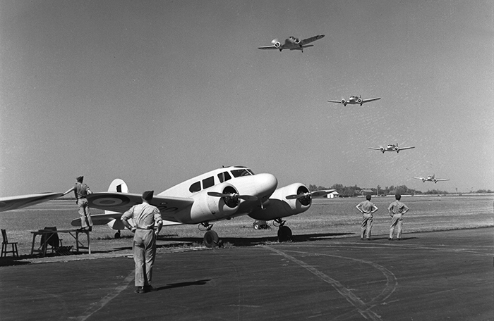 slide - In perfect formation, a flock of five Royal Canadian Air Force Cessna Cranes overflies a sixth on the opening day of No. 12 Service Flying Training School on July, 19, 1941, at Brandon, Manitoba.