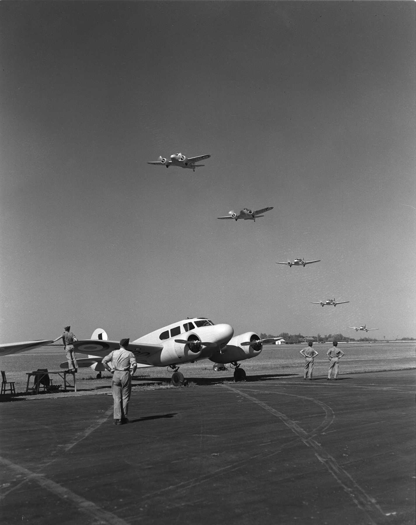 In perfect formation, a flock of five Royal Canadian Air Force Cessna Cranes overflies a sixth on the opening day of No. 12 Service Flying Training School on July, 19, 1941, at Brandon, Manitoba.