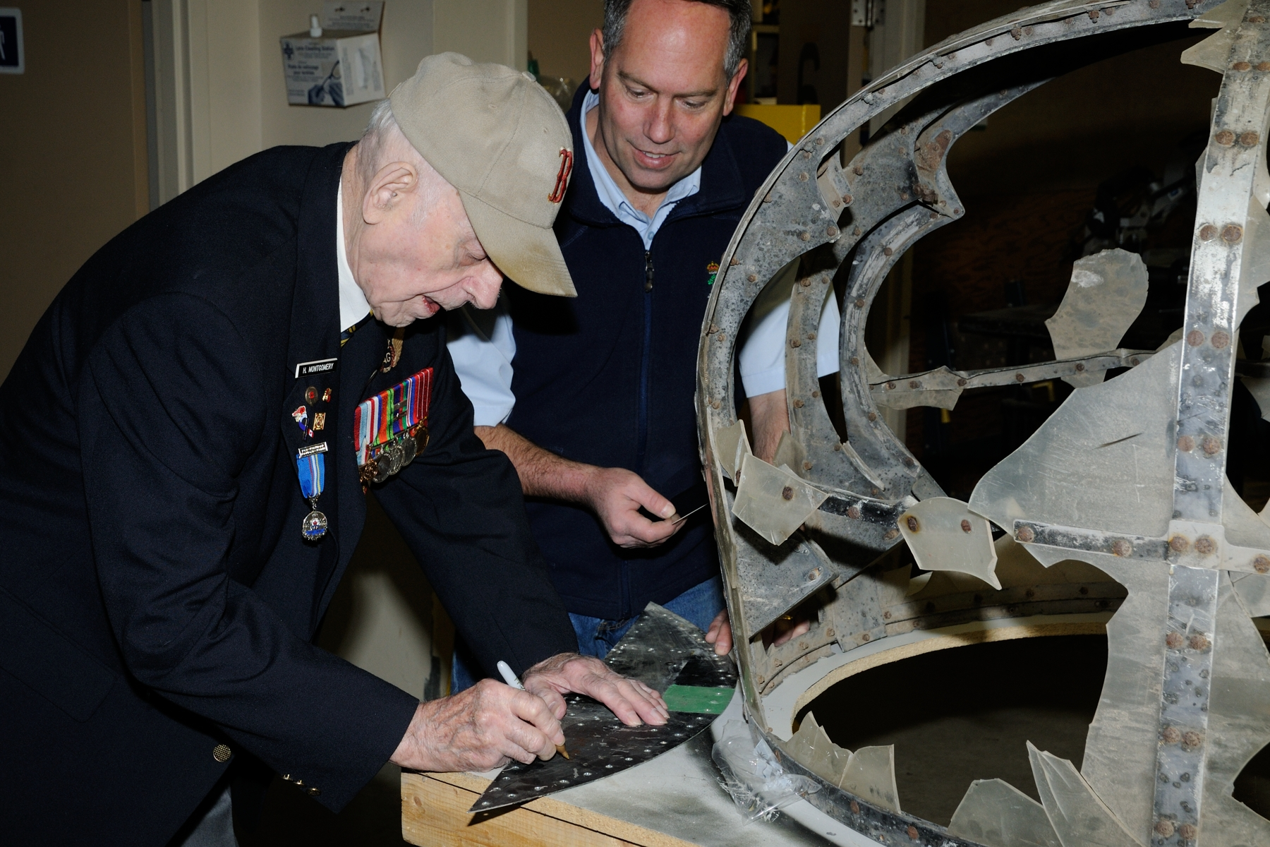On March 11, 2016, Clark Montgomery, a Second World War Lancaster middle upper gunner from Greenwood, Nova Scotia, signs his name on a plaque that will be a part of the mid-air turret on the restored Lancaster bomber aircraft at the Greenwood Military Aviation Museum. PHOTO: Sergeant Peter Nicholson, GP2016-0036