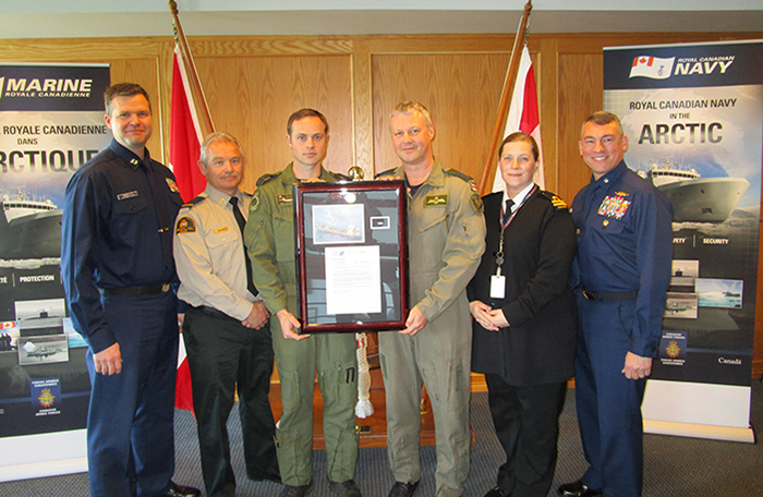 slide - CFB Esquimalt, British Columbia. 26 February 2016 – Left to Right: LT Karl Mueller, USCG; Mr. Frank Snelgrove, DFO; Capt. Dallas Bregg and Capt. Dave Howard, RCAF; Lt(N) Esther Nightingale, Royal Canadian Navy (RCN); Cdr Christopher Barrows, USCG; RAdm Gilles Couturier, RCN.