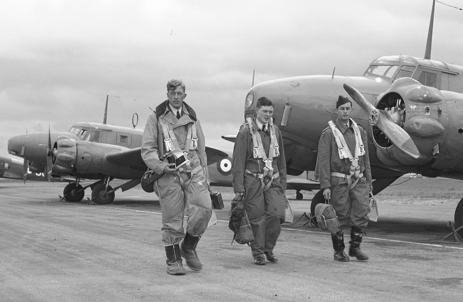 One of the photos on which the BCATP artwork on the 2016 Demonstration Hornet is based. In this photo, taken on June 4, 1941, at No. 1 Air Navigation School in Rivers, Manitoba, a trio of Commonwealth airmen walk down a line of Avro Ansons to the aircraft that will carry them on a navigation training flight. From left to right are Sergeant J. A. Mahood, Royal Air Force, Sergeant E.M.D. Romilly, Royal Canadian Air Force, and Sergeant W.H. Betts, Royal Australian Air Force. PHOTO: PL-3738, DND Archives