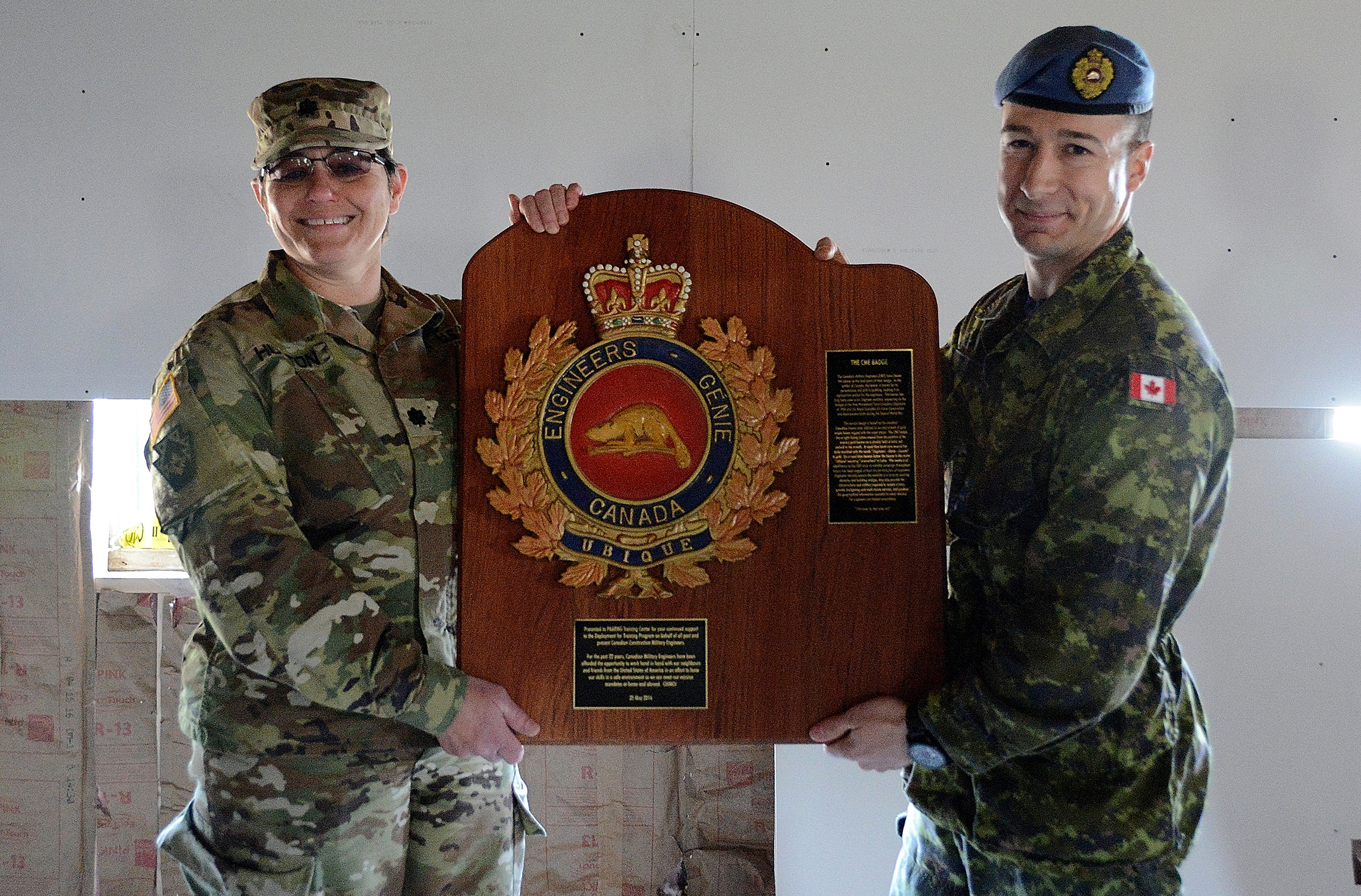 Royal Canadian Air Force Lieutenant-Colonel Jonathan Michaud (right), deputy director construction engineers at 1 Canadian Air Division Headquarters in Winnipeg, presents a commemorative plaque displaying the Canadian Forces' engineers badge to United States Army Lieutenant-Colonel Daneen Hutton, director of public works at Fort Indiantown Gap. The Canadian engineers have been coming to train at Fort Indiantown Gap for more than 20 years. PHOTO: Major Angela King-Sweigart, U.S. Army National Guard