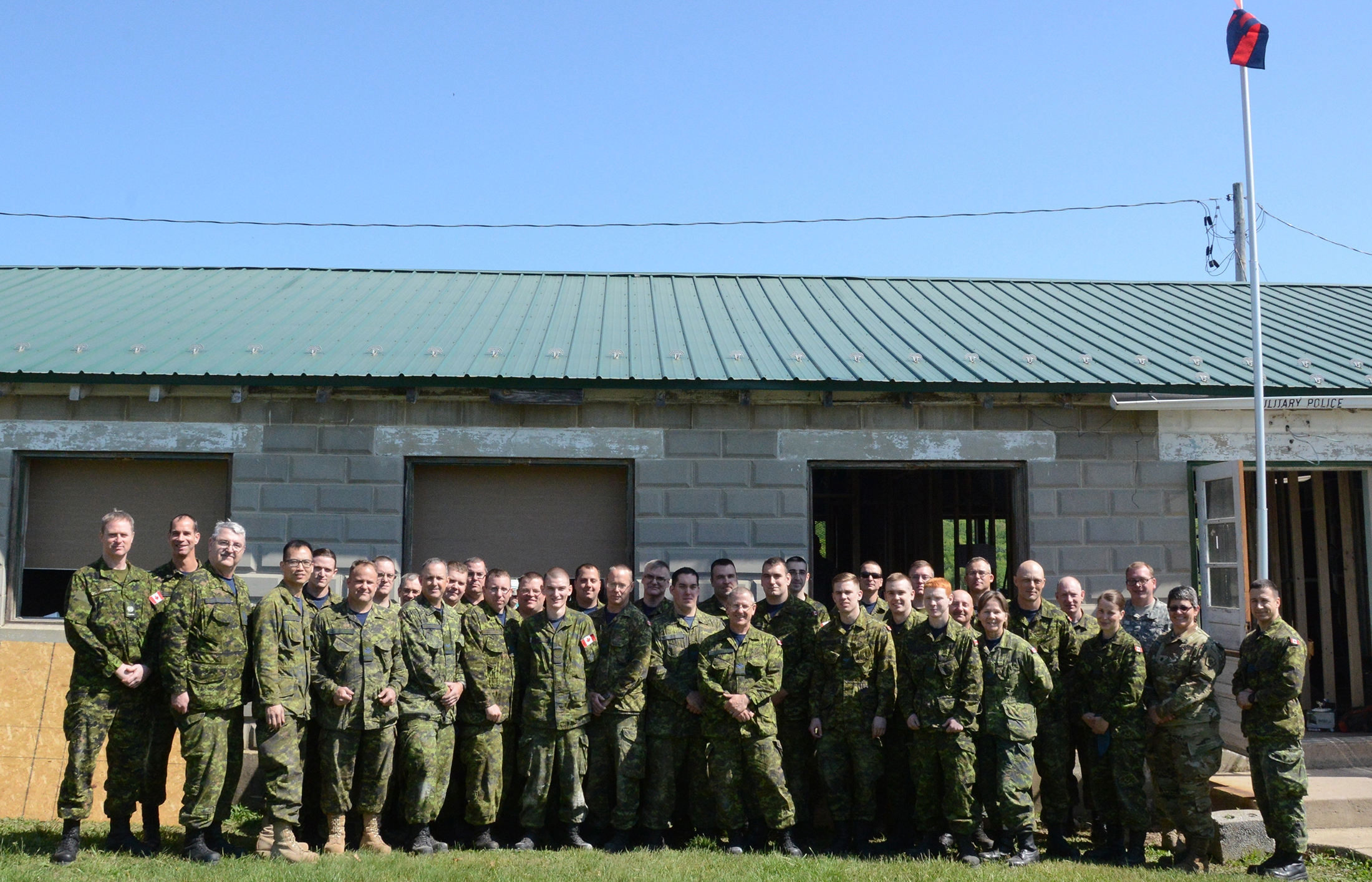 Canadian and American forces gather for a group shot in front of the building the Canadian personnel helped to renovate.