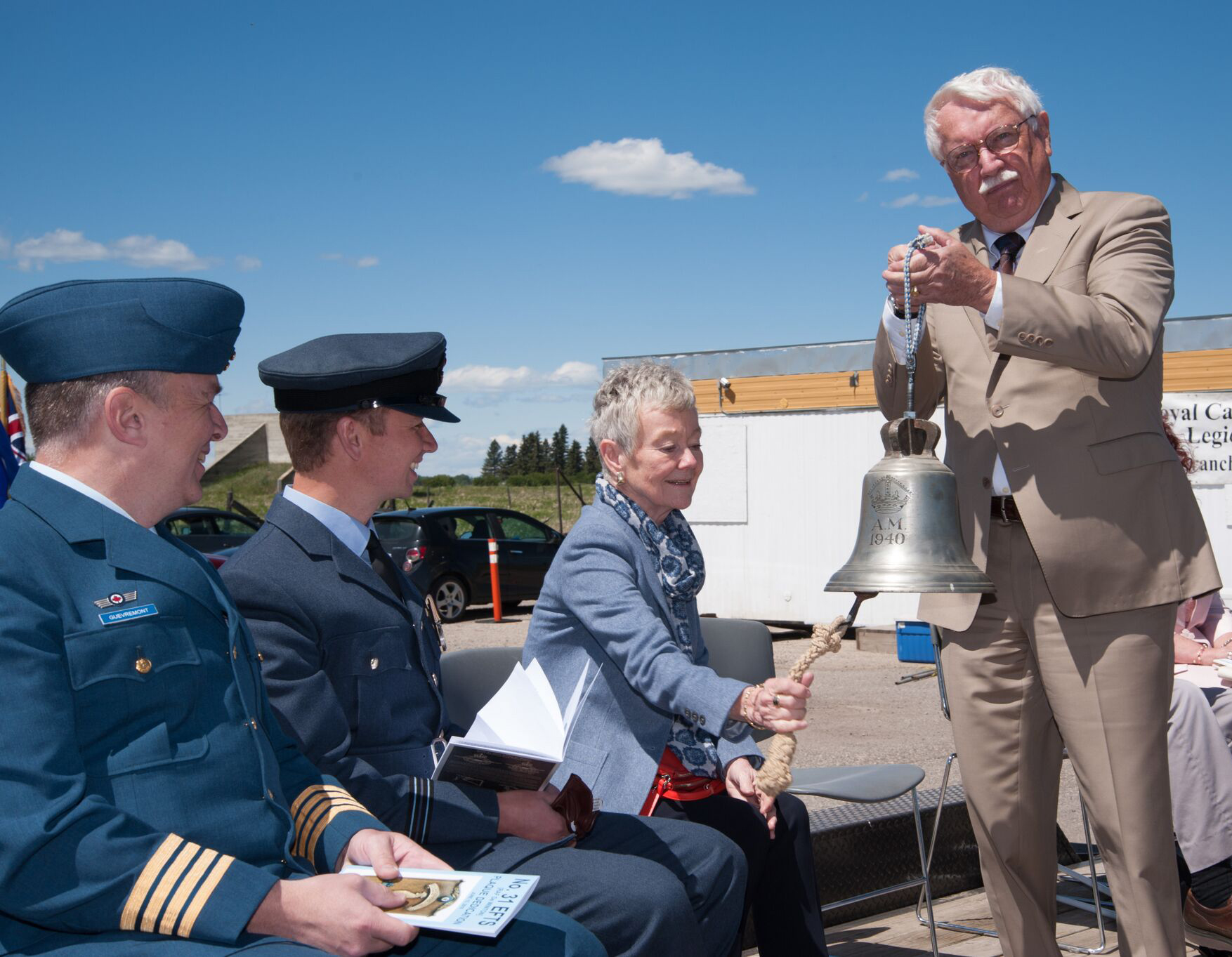 Susan Cowan rings a bell, held by the anniversary ceremony's MC, Mr.  Tim Johnston, to open the event. She is seated with Honorary Colonel Dr. Stéphane Gouvrement, far left, and Flight Lieutenant James Andrews of the Royal Air Force. PHOTO: Courtesy of Anne Gafiuk