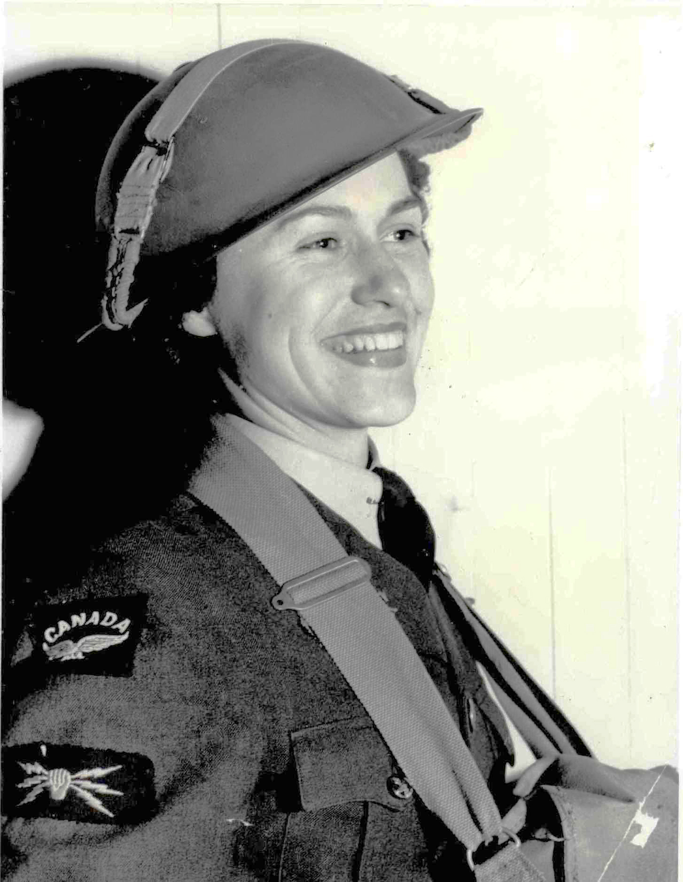 A black and white photo of a smiling young woman, in ¾ profile, wearing a helmet and a uniform with badges.
