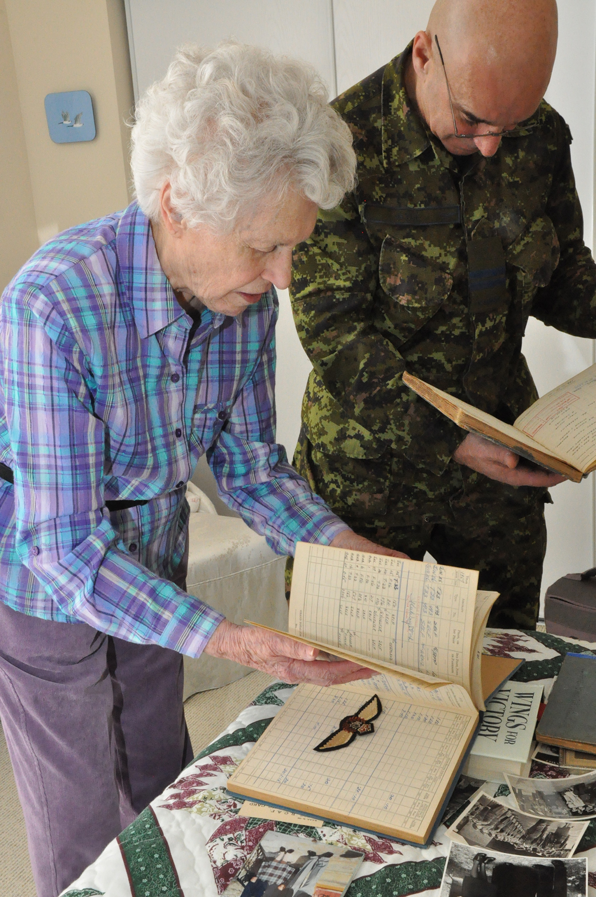 Allison MacKenzie and Captain Sandor Gyuk, 8 Wing Trenton, Ontario, heritage officer, look through her photographs, and the logbooks and RAF wings of her husband, Squadron Leader Andy MacKenzie, at her home in Belleville, Ontario. PHOTO: Ross Lees