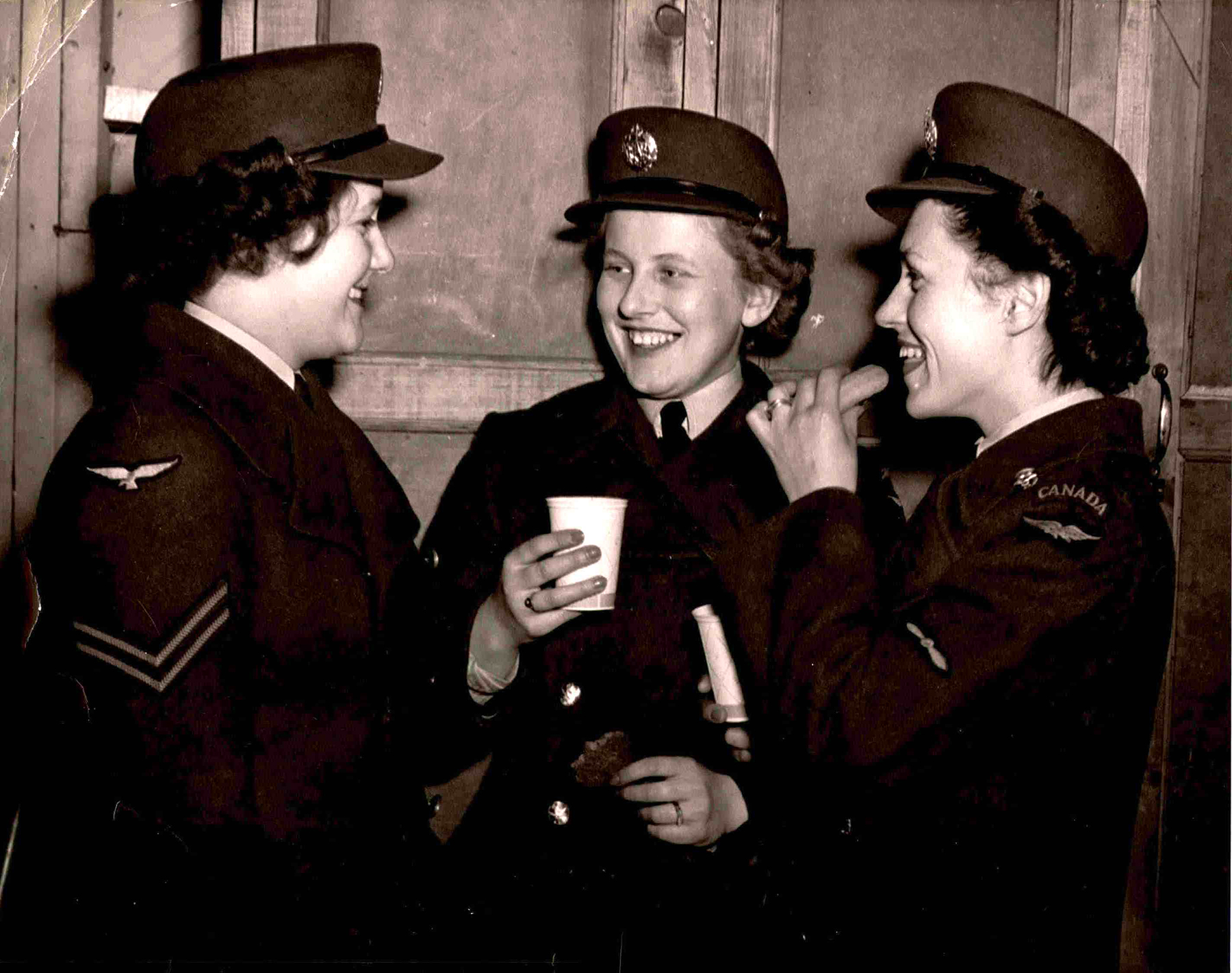"In an undated photograph, Allison ""Sparky"" MacKenzie, née Sparks, (right) and another RCAF member (centre), enjoy coffee and a doughnut upon their arrival in back in Canada. PHOTO: Courtesy of Allison MacKenzie"