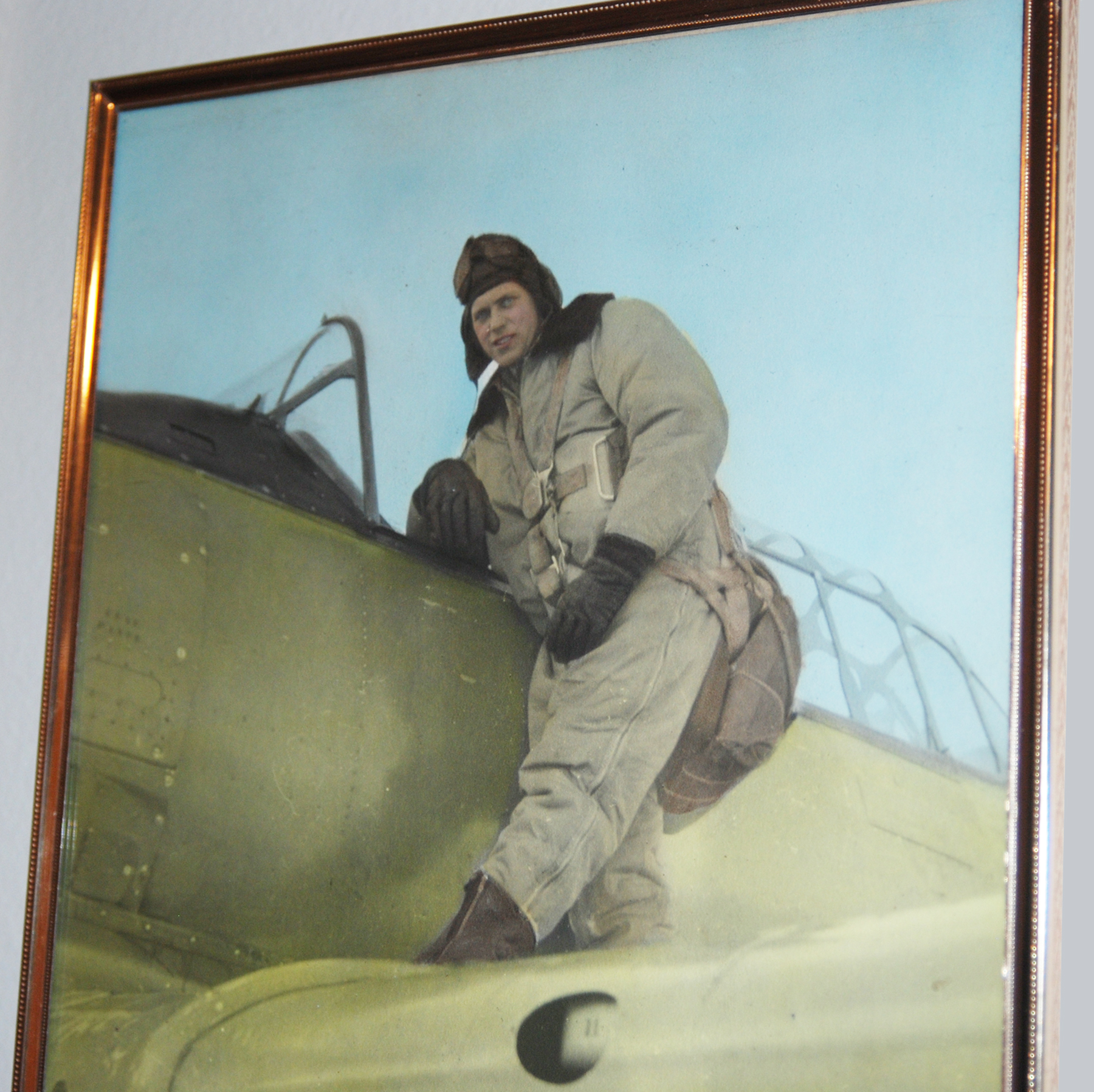 Wearing his flight suit, Flying Officer John Newell stands on the wing of his Second World War aircraft in a framed, undated image hanging in the Newells' home in Ottawa, Ontario. PHOTO: Alexandra Baillie-David