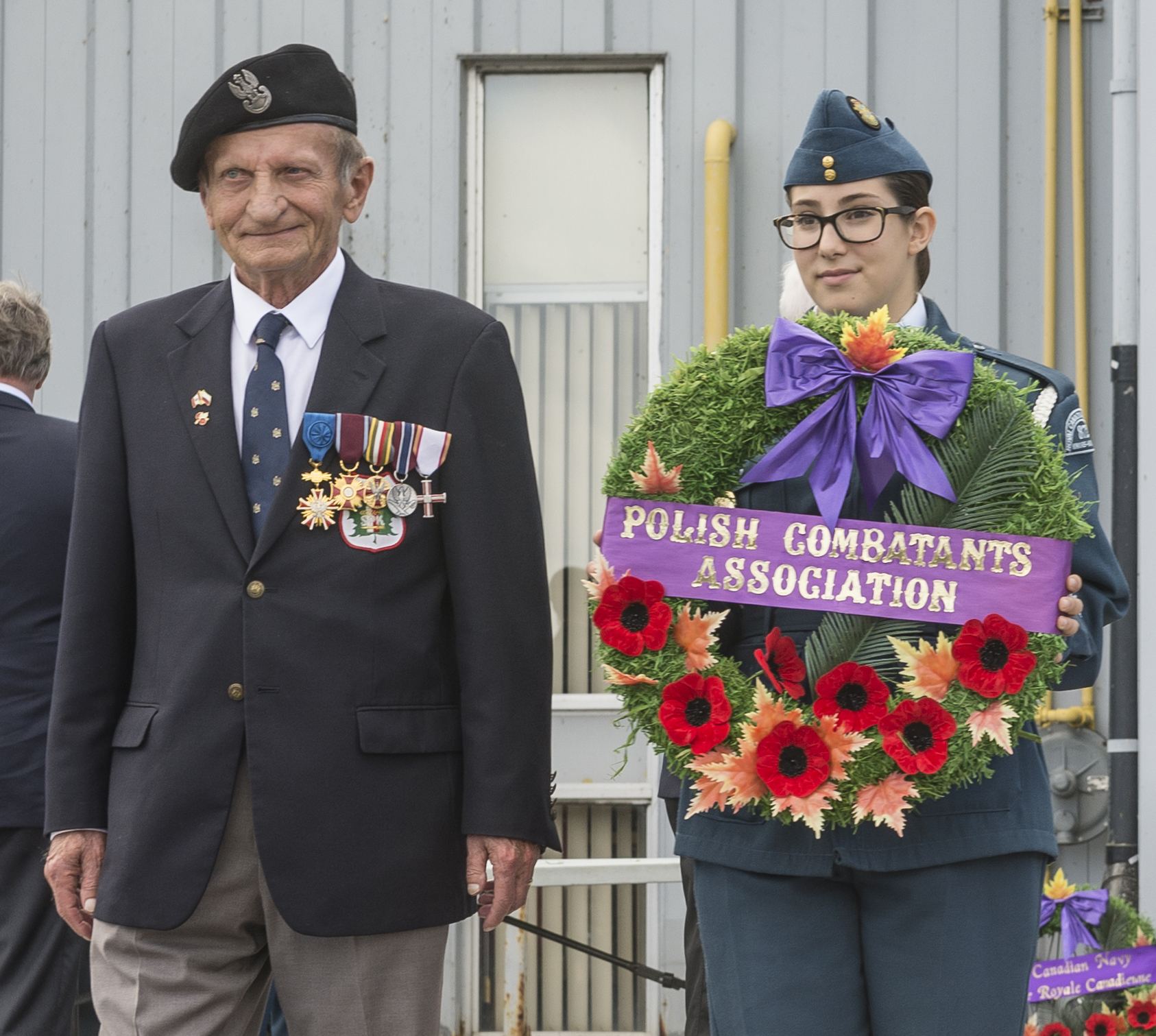 "Jerzy Kulczycki, Ph.D., president of the Polish Combatants' (Veterans) Association in Canada, Branch No. 8 in Ottawa, accompanied by Warrant Officer Second Class Emelie Matta from the Kiwanis Kanata Squadron of the Royal Canadian Air Cadets, prepares to lay a wreath on behalf of the Polish Combatants Association during the national Battle of Britain ceremony held September 18, 2016, at the Canada Aviation and Space Museum. ""Number 303 Squadron, a Polish squadron . . . scored the most victories during the Battle,"" noted Wing Commander Simon Hulme of the Royal Air Force during his remarks at the ceremony. PHOTO: Corporal Alana Morin, FA03-2016-0032-052"