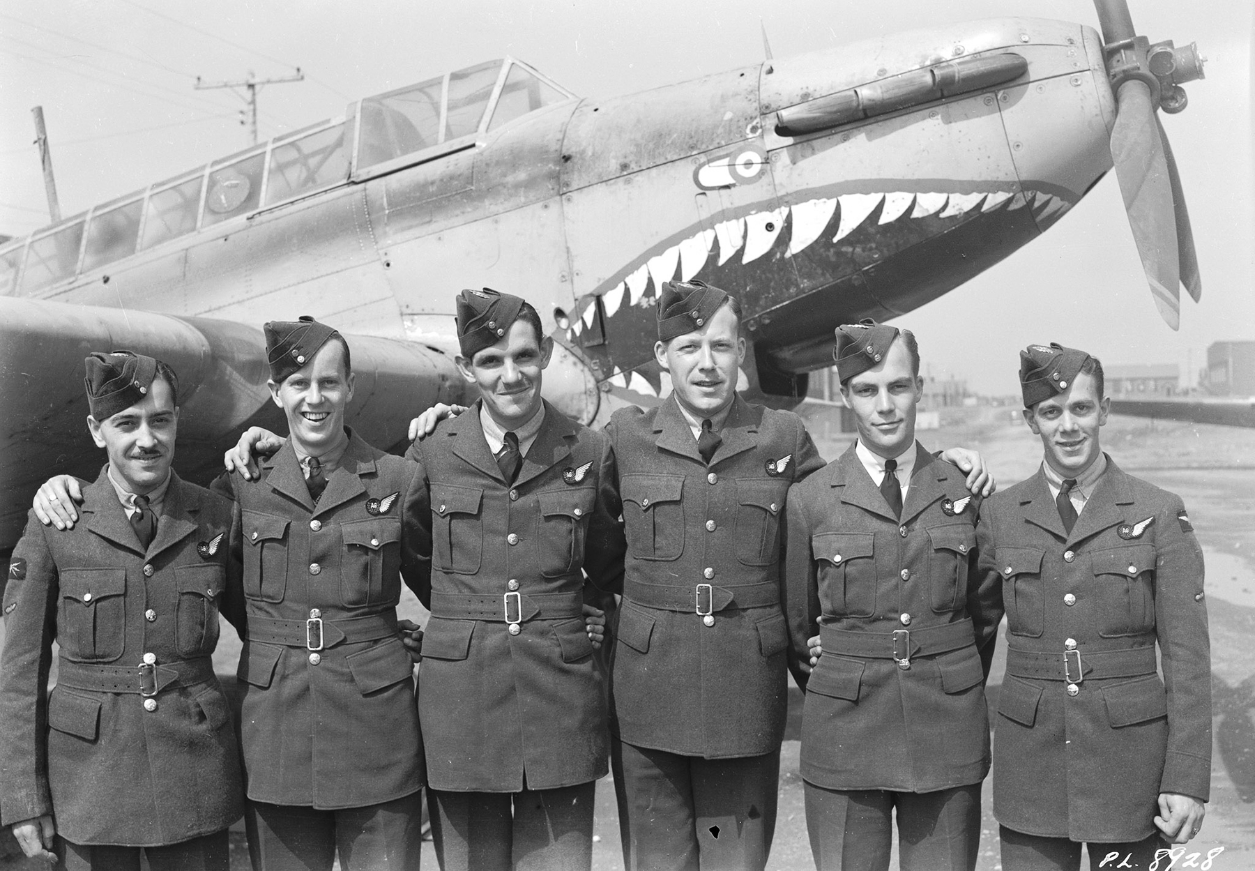 Standing beside a menacing Fairey Battle trainer aircraft, Leading Aircraftman J.L.H. Gougeon (left), Leading Aircraftman A.C. Reay, Leading Aircraftman J.C.E.M. Brosseau,; Leading Aircraftman F.G. Bourque, Leading Aircraftman D.W. Fraser, and Leading Aircraftman J.E.J.P. St. Michel, all from Québec, are part of the May 20, 1942, graduating class of Course #30, 1&2, at No. 9 Bombing and Gunnery School on RCAF Station Mont-Joli, Québec. PHOTO: DND Archives, PL-8928
