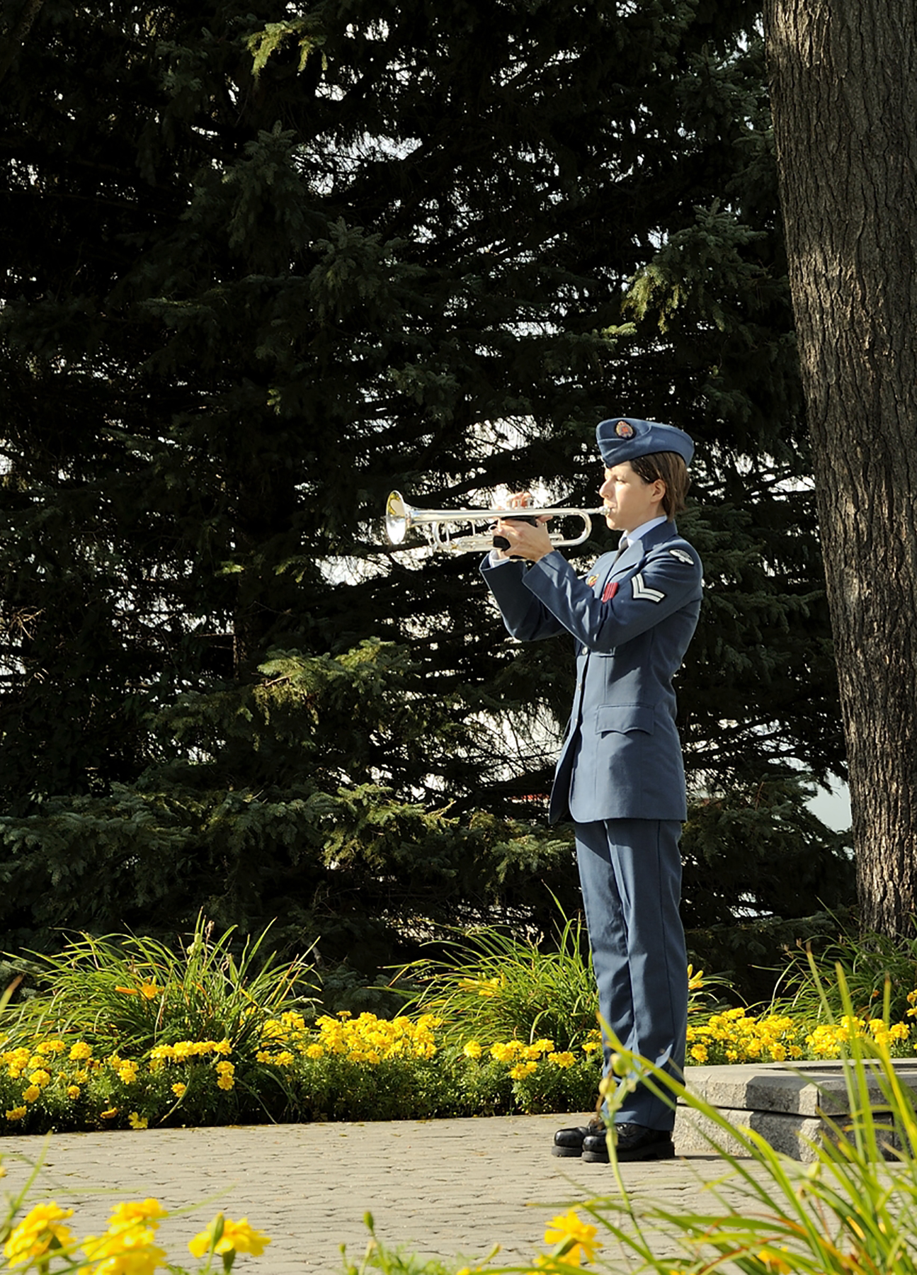 "Corporal Christine Savoie sounds ""Reveille"" at the Canadian Forces Base Borden, Ontario, Air Force cenotaph on September 18, 2016, during the Battle of Britain parade. PHOTO: Corporal Aydyn Neifer, BM03-2016-0272-06"