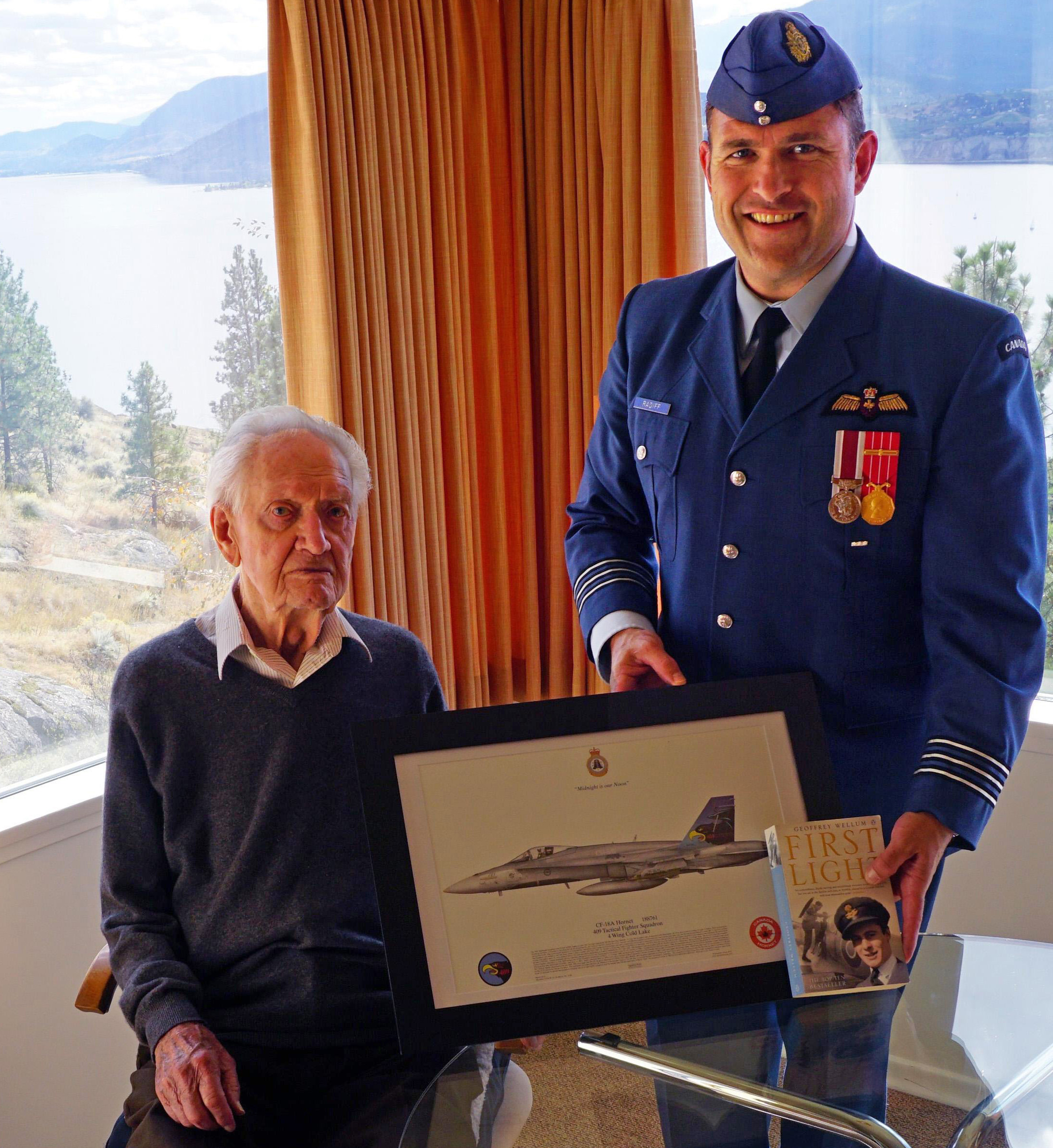 Lieutenant-Colonel William Radiff, commanding officer of 409 Squadron, presents Squadron Leader (retired) John Hart with a framed 409 Squadron commemorative print.  Squadron Leader John Hart presented Lieutenant-Colonel William Radiff a copy of the book First Light, written by Battle of Britain pilot Geoffrey Wellum, explaining that it is a very accurate description of what it was like to be a fighter pilot in the Second World War. PHOTO: Submitted