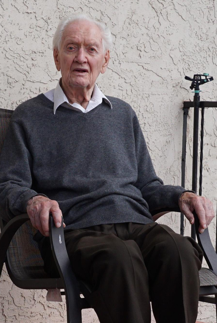 An elderly man is seated in a chair.