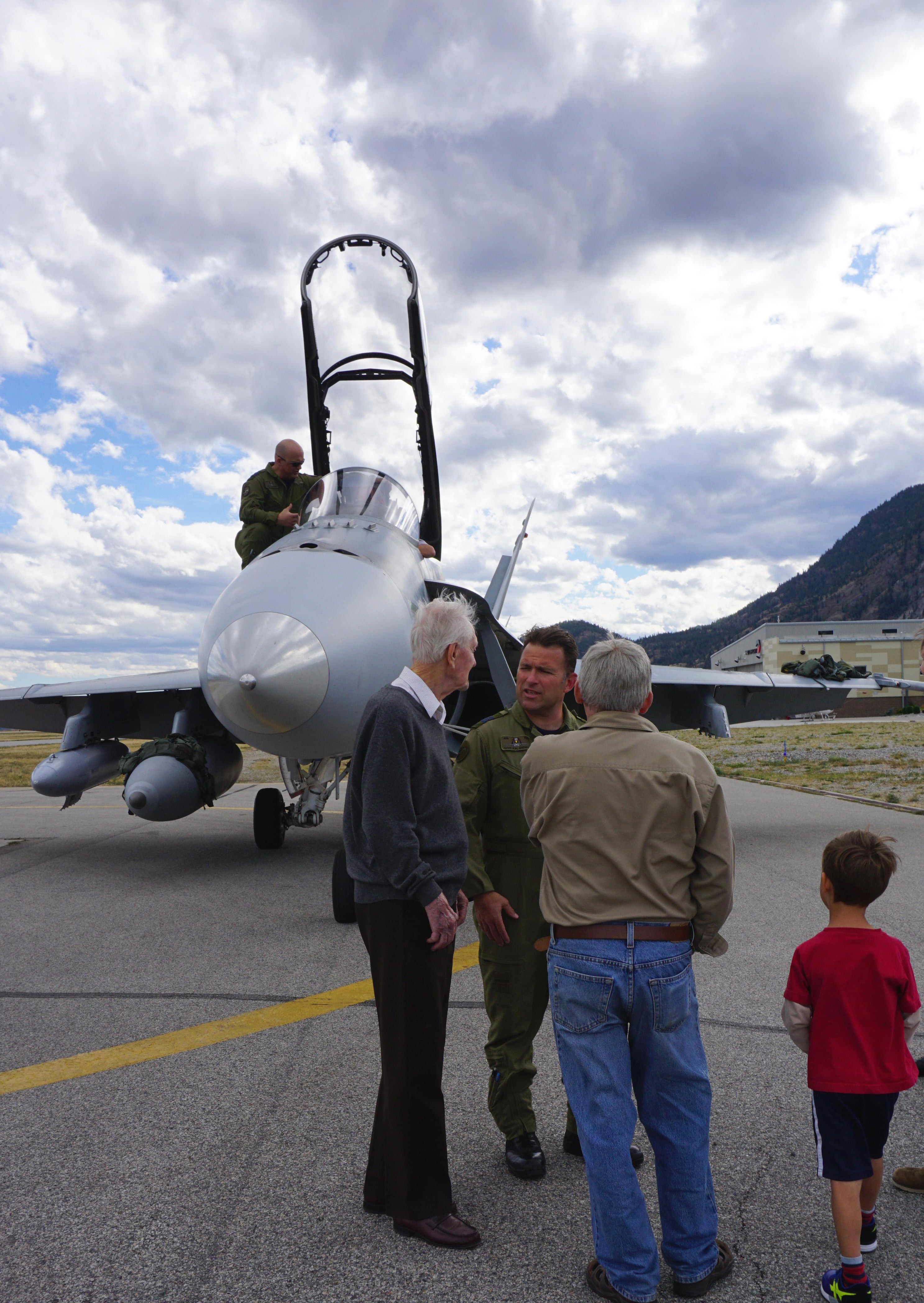 Members of Squadron Leader (retired) Hart and his family visit the two CF-188 Hornets and their crews at the Penticton Regional Airport in British Columbia. The two CF-188s, from 409 Tactical Fighter Squadron at 4 Wing Cold Lake, Alberta, conducted a flyby near Squadron Leader Hart's home on Battle of Britain Sunday – September 18, 2016 – in honour of his 100th birthday and his service during the Battle of Britain. Squadron Leader Hart is believed to be the last surviving Canadian-born Battle of Britain pilot. PHOTO: Submitted