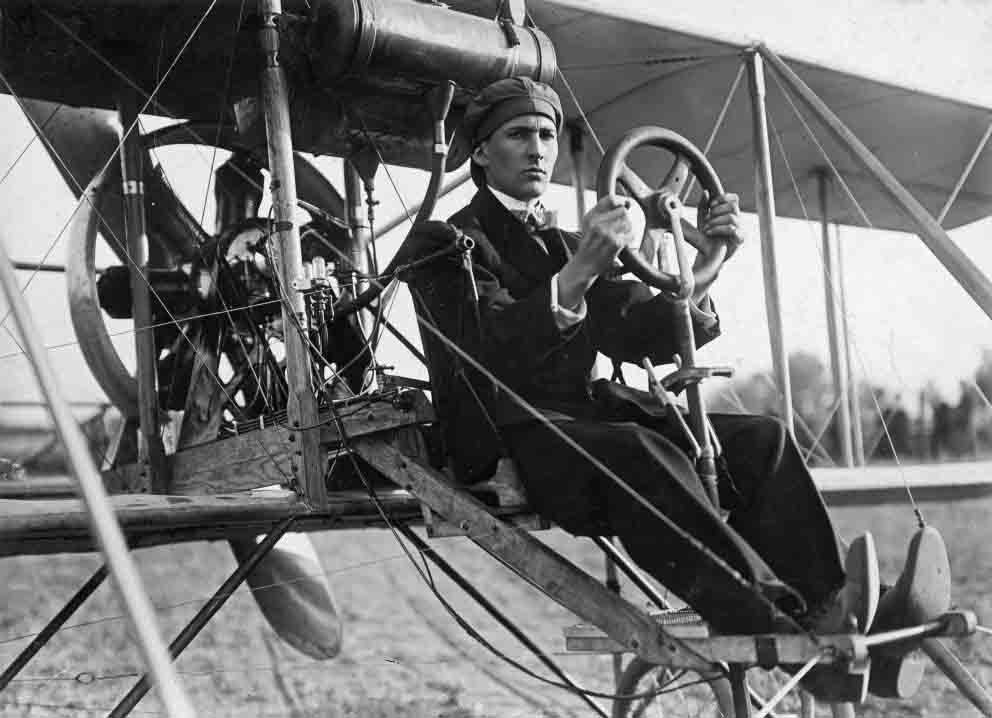 A black and white photo of a young man sitting at the con-trols of a very old aircraft made of thin wires, wooden struts and fabric