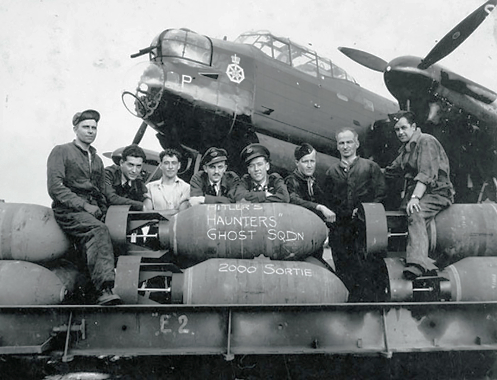 In a black and white photograph, eight men wearing uniforms or coveralls gather around or sit on bombs beside an aircraft.