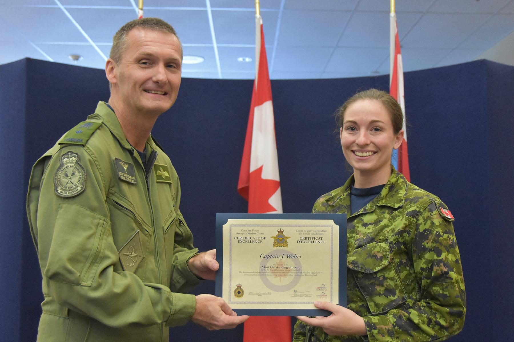 Brigadier-General David Cochrane, 2 Canadian Air Division commander, presents Captain Jenna Wolter, a logistics (finance) officer, the award for outstanding student on Air Power Operations Course Serial 1601, for demonstrating academic excellence, professional attitudes, a solid teamwork ethic, and a high level of professional deportment while garnering the respect of fellow students and directing staff. PHOTO: DND