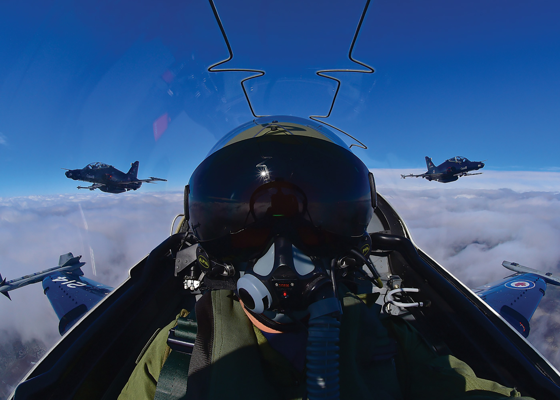 Above the clouds, a close-helmeted pilot in a canopied cockpit stares forward into the camera, while two aircraft follow and flank his.