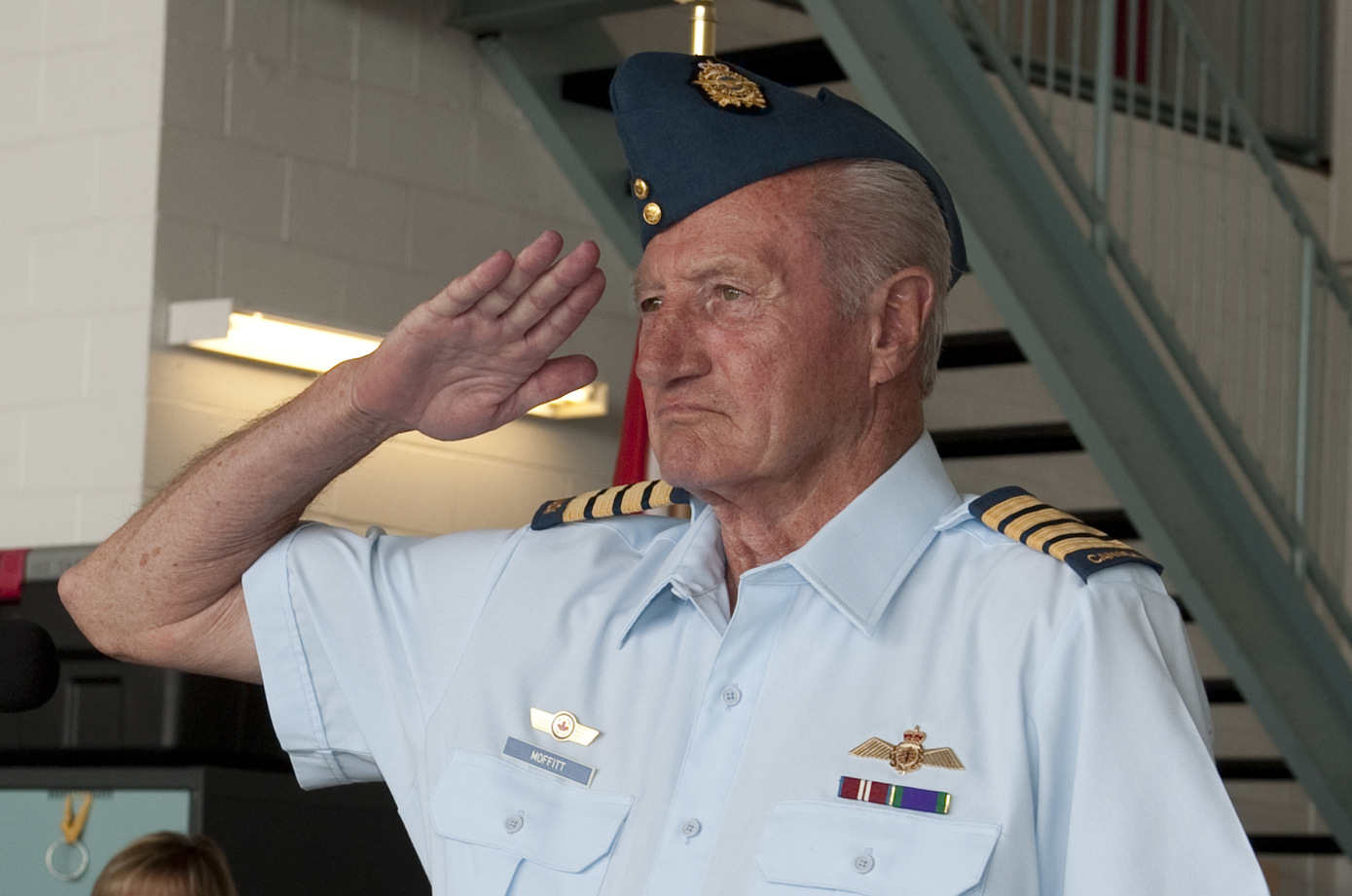 A head and shoulders photo of an older man in an air force uniform, saluting.