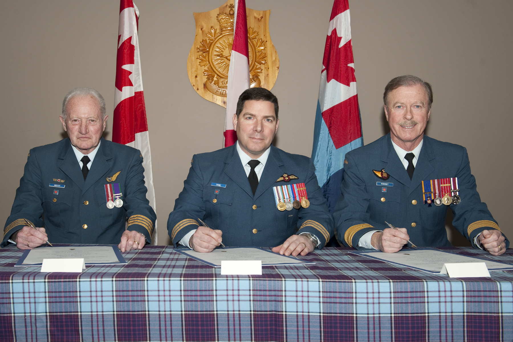 Lieutenant-Colonel Kevin Toone, then-commander of 9 Wing Gander, presides over the wing's honorary colonel change of appointment ceremony during which Honorary Colonel Fred Moffitt (left) took over the post from Honorary Colonel Bill Mahoney (right). The ceremony took place January 21, 2015. Honorary Colonel Moffitt, who served in the Royal Air Force, wears the Queen Elizabeth II Diamond Jubilee Medal, the British General Service Medal and his RAF navigator wing. PHOTO: Master Corporal Sue Howell