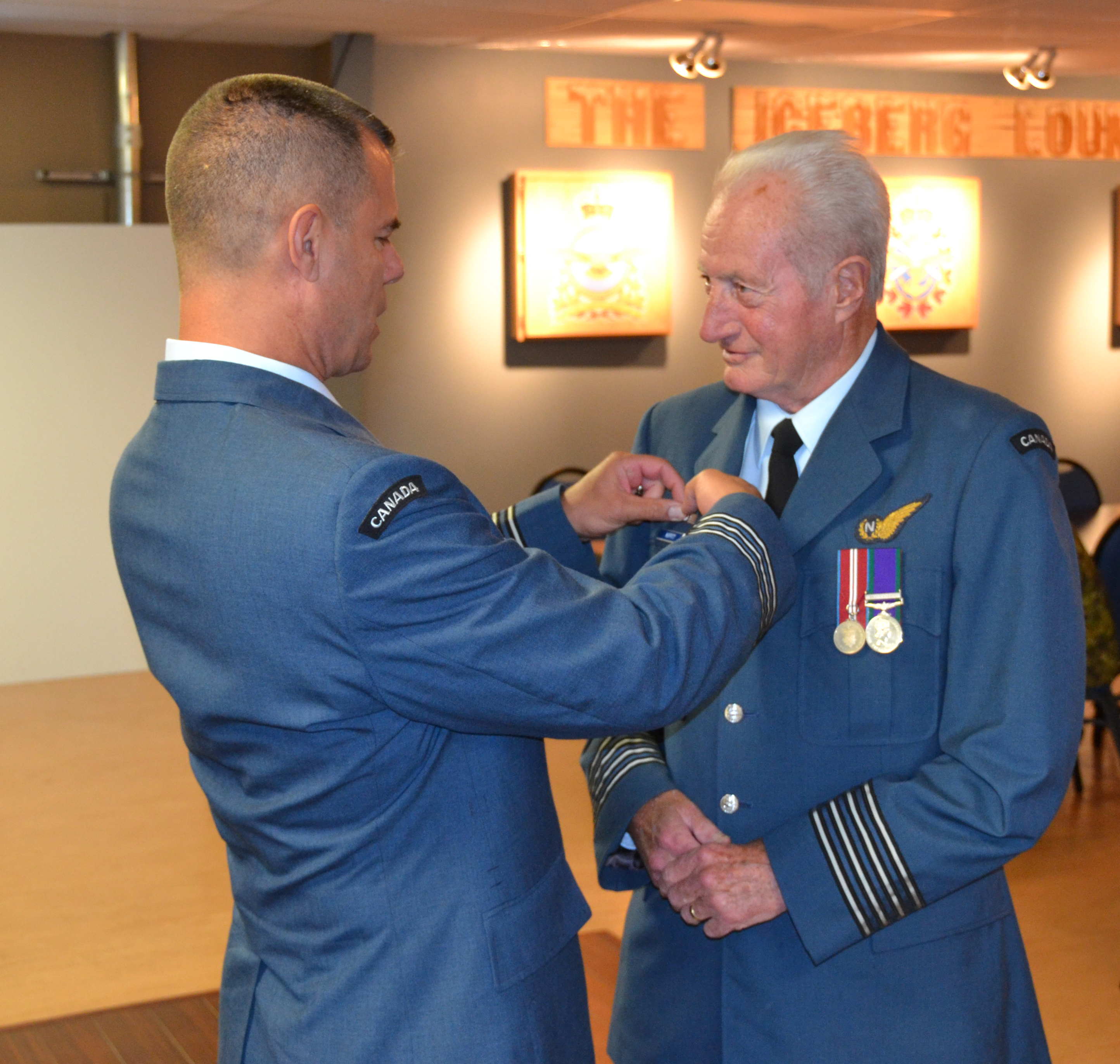 Lieutenant-Colonel Pierre Haché, commander of 9 Wing Gander, Newfoundland and Labrador, pins honorary colonel wings on Honorary Colonel Fred Moffitt's tunic. Honorary Colonel Moffitt served as honorary colonel of the wing from December 2014 until his death on January 17, 2017. PHOTO: Submitted