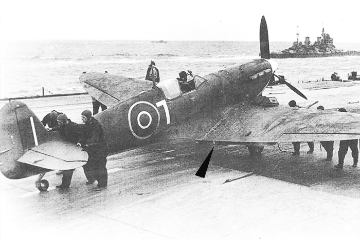 A Supermarine Seafire is readied for takeoff late in the war. Even though Seafires were modified for carrier operations, they still lacked takeoff flaps (until the Seafire 47). The Royal Navy opted to keep the simple wooden block system employed by Spitfires in the Club Runs to Malta. The blocks that keep the flaps down for takeoff can just be seen in this photograph. There are two per side as Spitfire flaps are split into two sections. PHOTO: Royal Navy