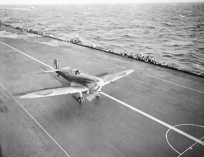 "A Supermarine Spitfire Mk VbT ""Trop"", with a 90-gallon (409-litre) slipper tank just visible beneath her fuselage, thunders at full power down the flight deck of HMS Eagle during a Club Run. PHOTO: Imperial War Museum"