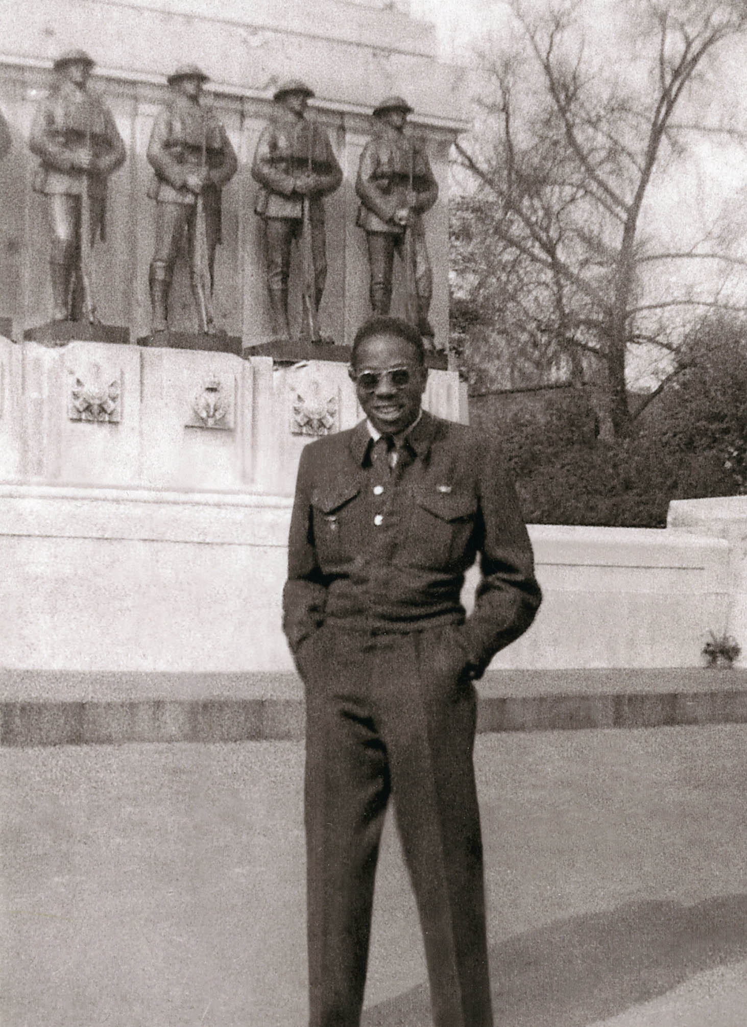 A vintage black and white photo of a man in a military uniform standing in front of a commemorative monument