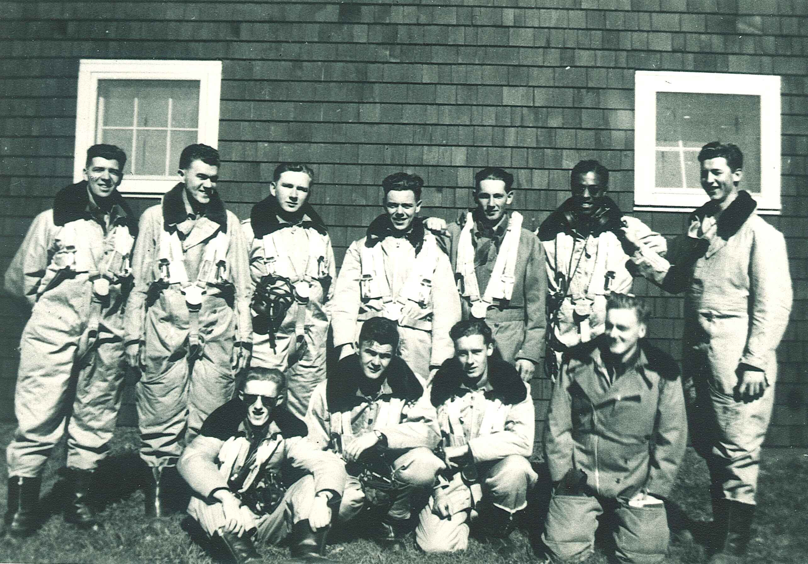 An old black and white photo of a group of 11 men in bulky air force flying suits, standing or kneeling in front of the shingled exterior wall of a building.