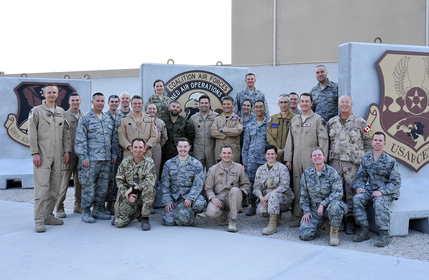 Wearing his nation on his sleeve, Major John Blair (second row, right) stands outside the Air Operations Centre in Kuwait with his colleagues from 26 coalition nations. PHOTO: USAF