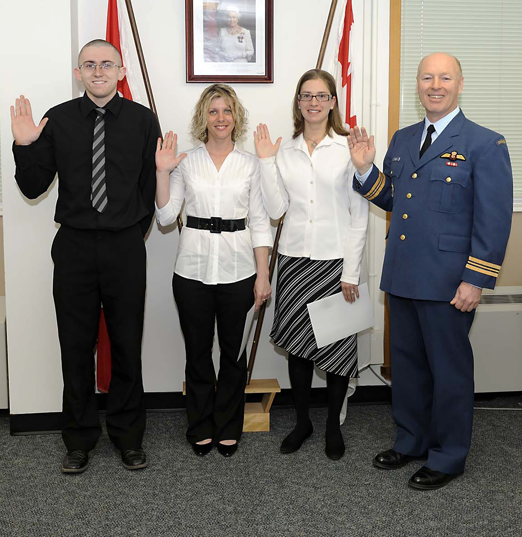 On April 1, 2010, in the United States Conference room of building 7A at 22 Wing North Bay, Ontario, Private Donivan Hart (left), Officer Cadet Christine Bolan, and Private Anne-Marie Dubois-Mayhew are sworn in as new members of 22 Wing Air Reserve by 22 Air Reserve Flight's commander, Major John Blair. PHOTO: Corporal Samantha Crowe, NB2010-0060-07