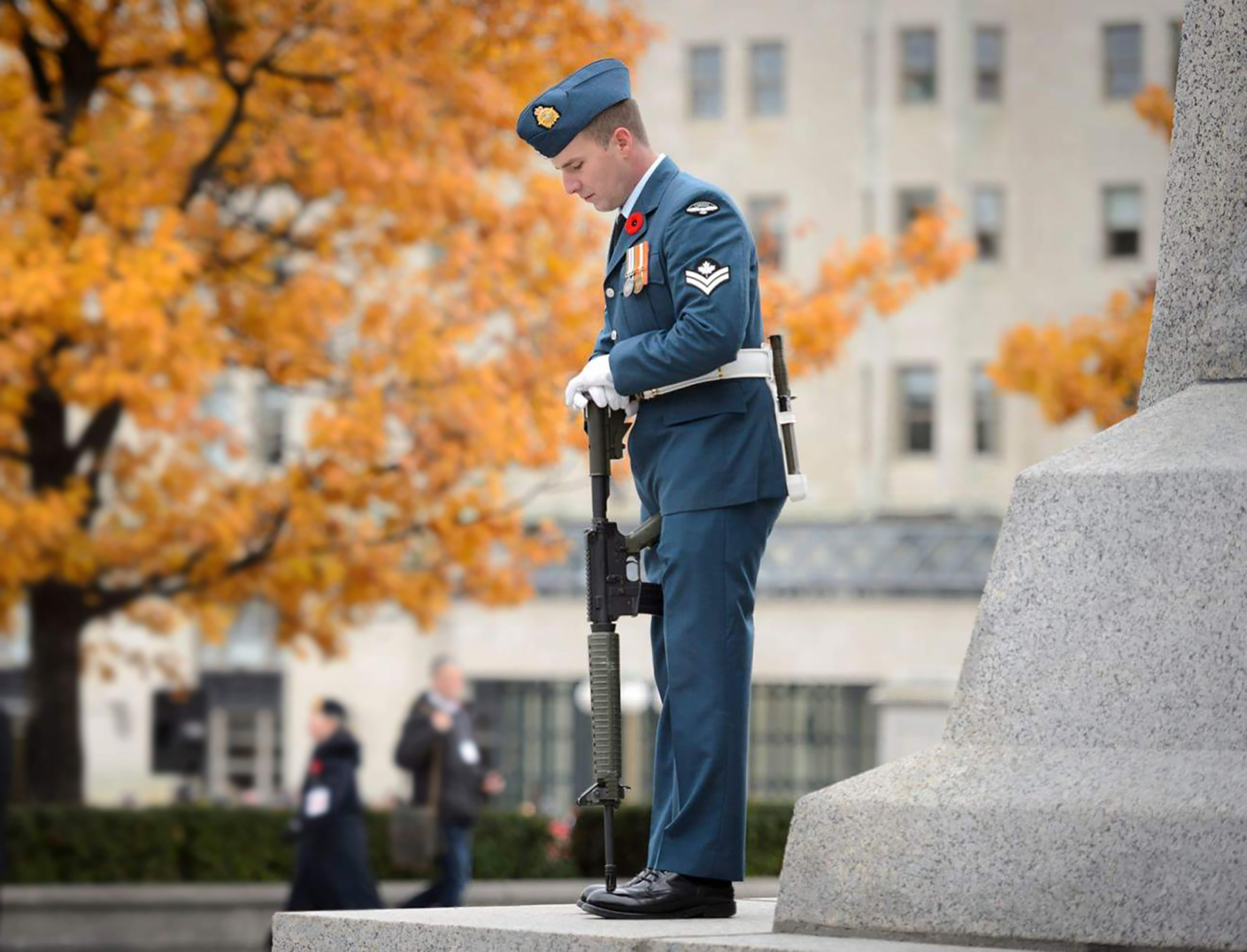 A man wearing a poppy on his blue military uniform stands with his head bowed and his rifle reversed at a war memorial.