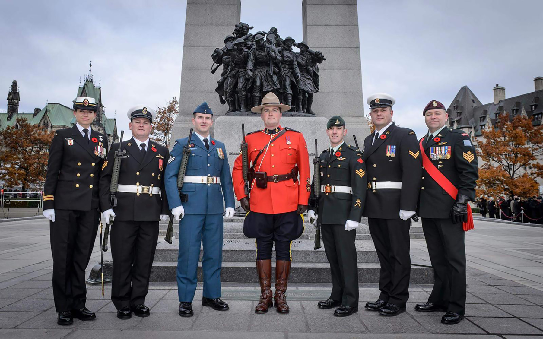 On November 11, 2016, Nursing Officer Lieutenant(N) Ashley Atkins (high readiness critical care nursing officer)(left); Sentry Commander Petty Officer 2nd class Pascal Desjardins (senior sonar operator); Royal Canadian Air Force Sentry Master Corporal George Arsenault (aerospace control instructor); Royal Canadian Mounted Police Sentry Corporal Curtis Barrett (police explosives technician); Canadian Army Sentry Master Bombardier Guillaume Lemay (observation post second-in-command); Royal Canadian Navy Sentry Leading Seaman Kyle Ruttan (supply technician); and Special Guest of the Chief of the Defence Staff Sentry Sergeant Lorne Ford (unit emplaning officer) gather for a photograph at the National War Memorial in Ottawa, Ontario, before the Remembrance Day Ceremony. PHOTO: Corporal Michael MacIsaac
