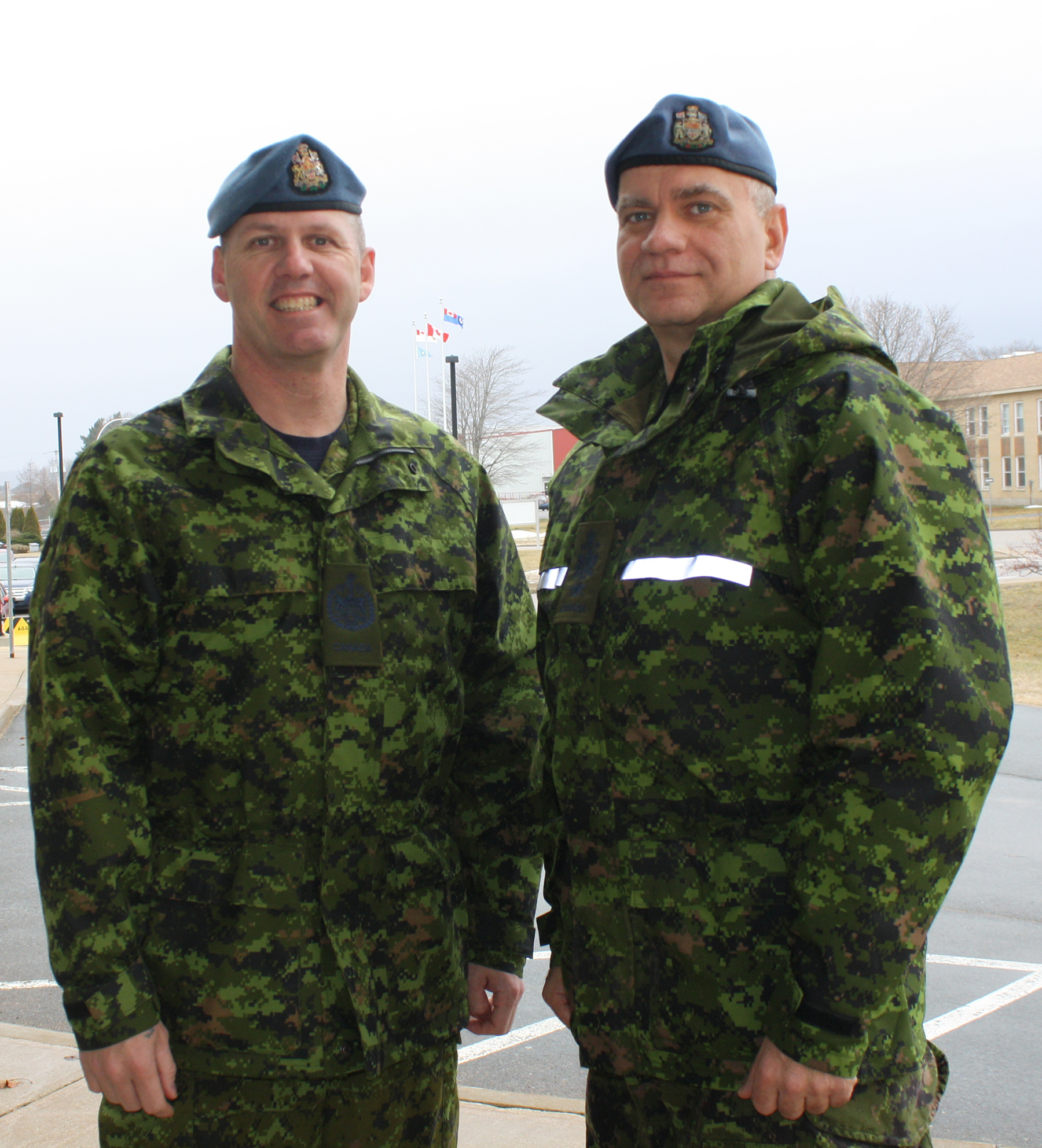 Two men stand side by side wearing black, green and tan disruptive pattern uniforms and blue berets.