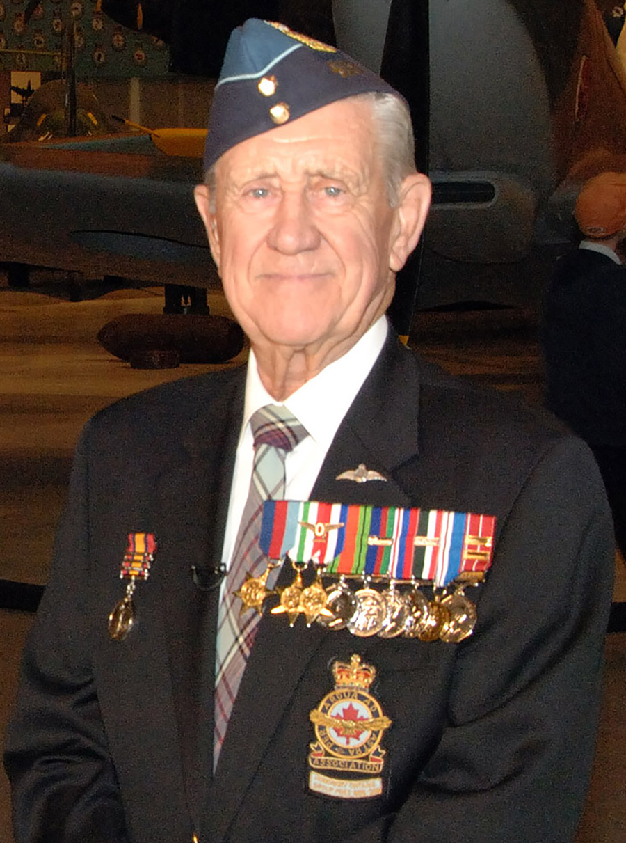 An elderly man with medals on his dark navy blazer smiles at the camera.