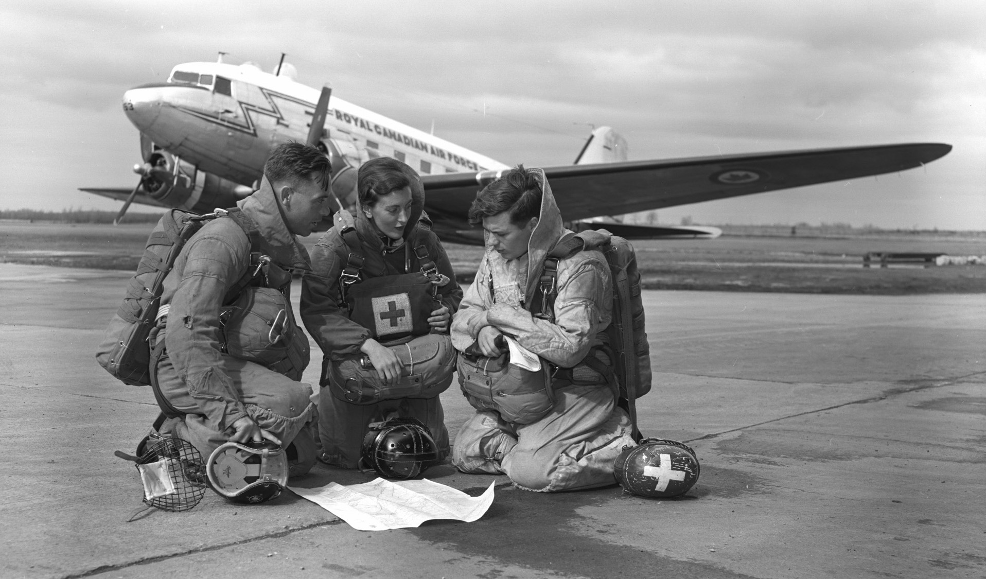 In this undated photo, Para Rescue Team 29811 – Leading Aircraftman C.L. Hegadorne, Flying Officer (Nursing Sister) E.R. Kelly and Corporal R.E. Crawford – study a map before take-off. PHOTO: DND Archives, PL-87049