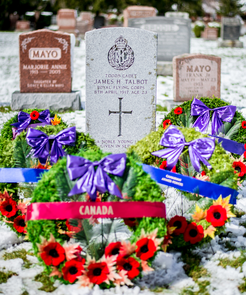 A photo of a military grave marker with remembrance wreaths placed in front of it.