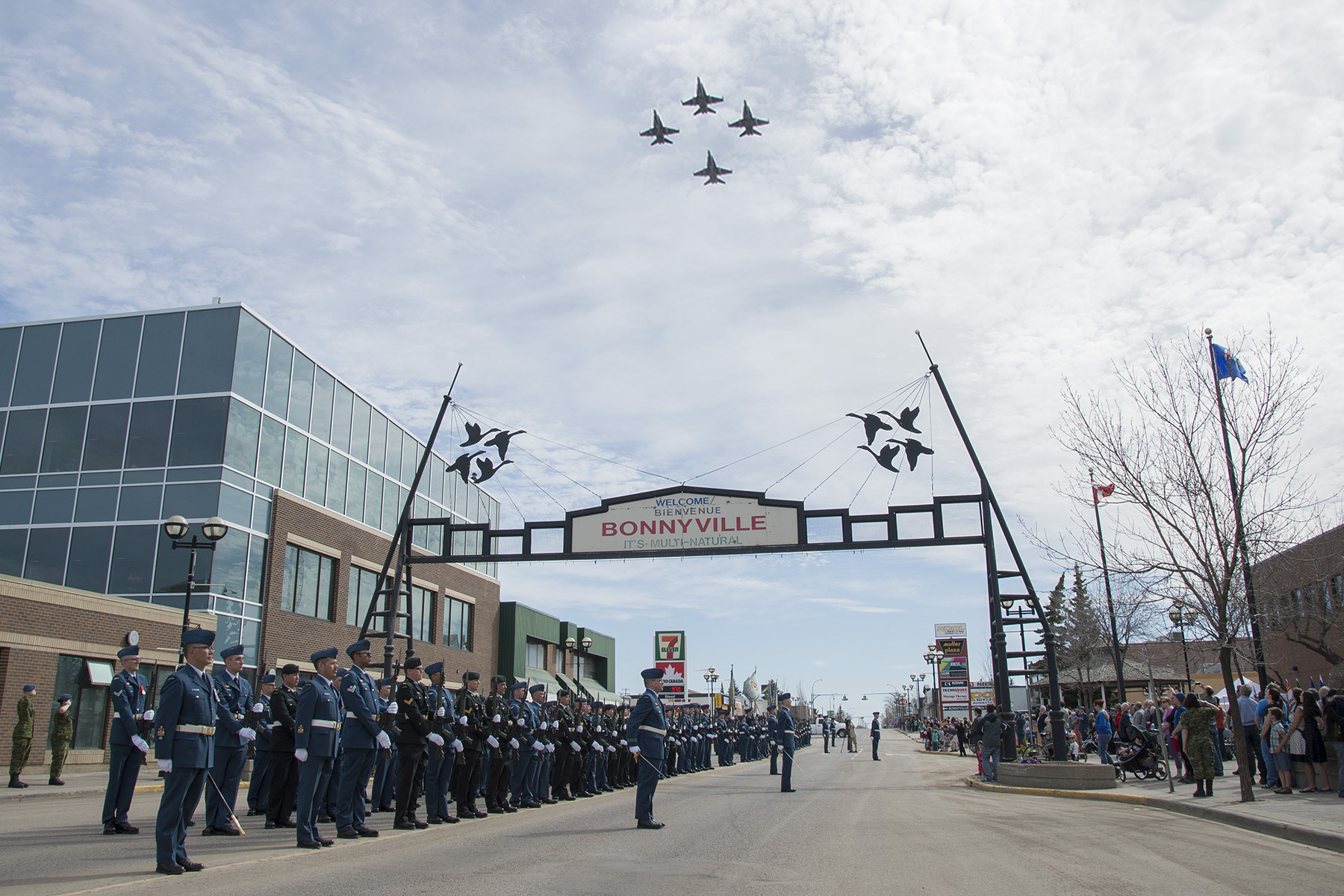 Four jet aircraft overfly three long lines of people in blue or black uniforms facing an equally long line of people in civilian dress across a business street of a town.