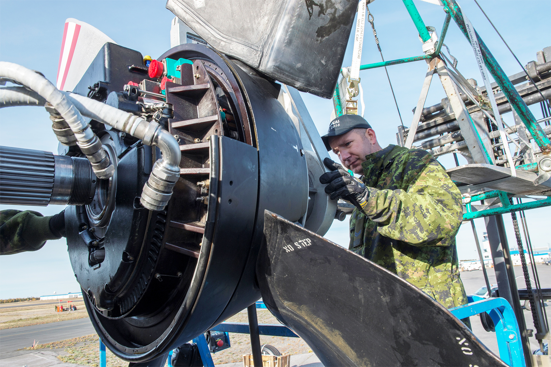 Corporal Dan Roman, an avionics technician, performs repairs on a propeller of a CC-130 Hercules cargo airplane during the National Search and Rescue Exercise in Yellowknife, Northwest Territories, on September 21, 2016. PHOTO: Master Corporal Pat Blanchard, IS03-2016-0035-008
