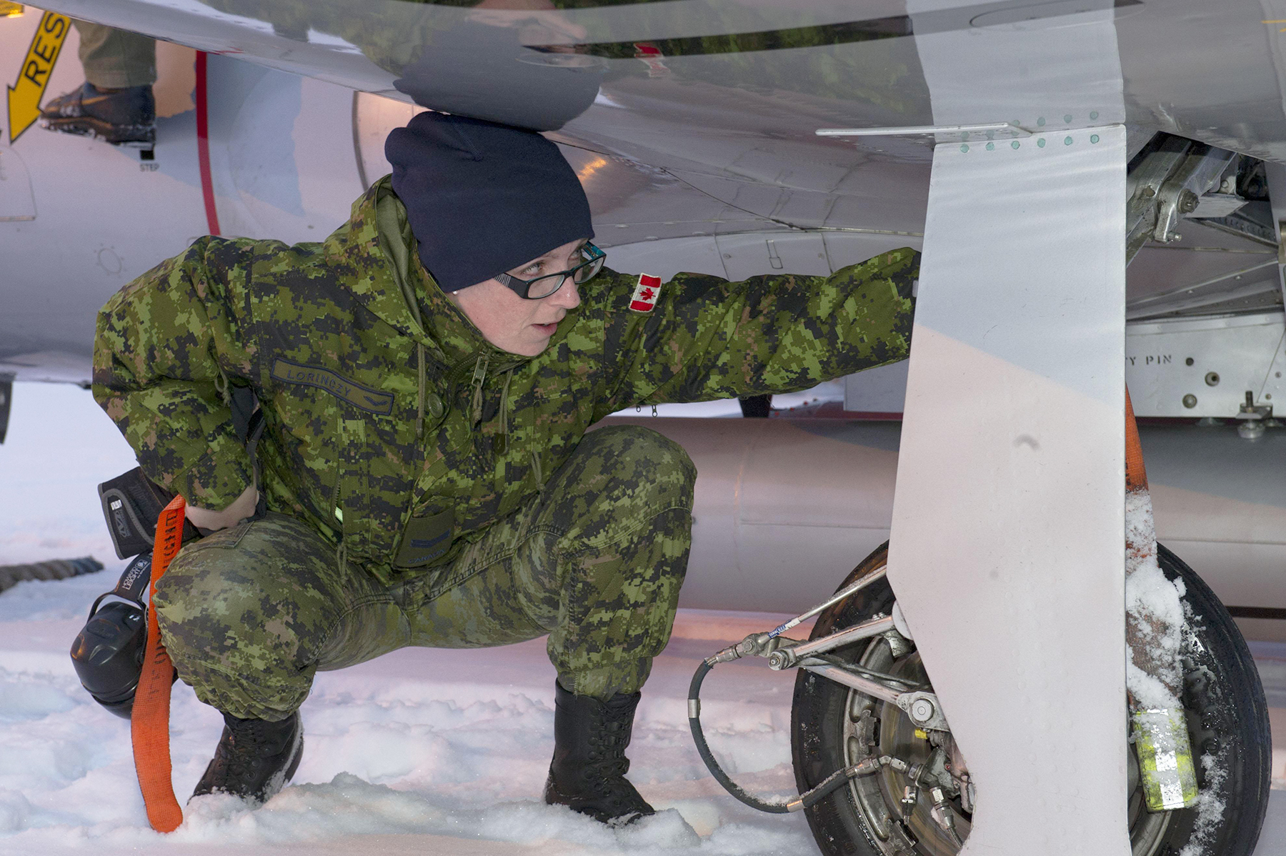 A woman wearing green camouflage clothing, black boots and a dark blue tuque squats by the landing gear of an aircraft and reaches for something.