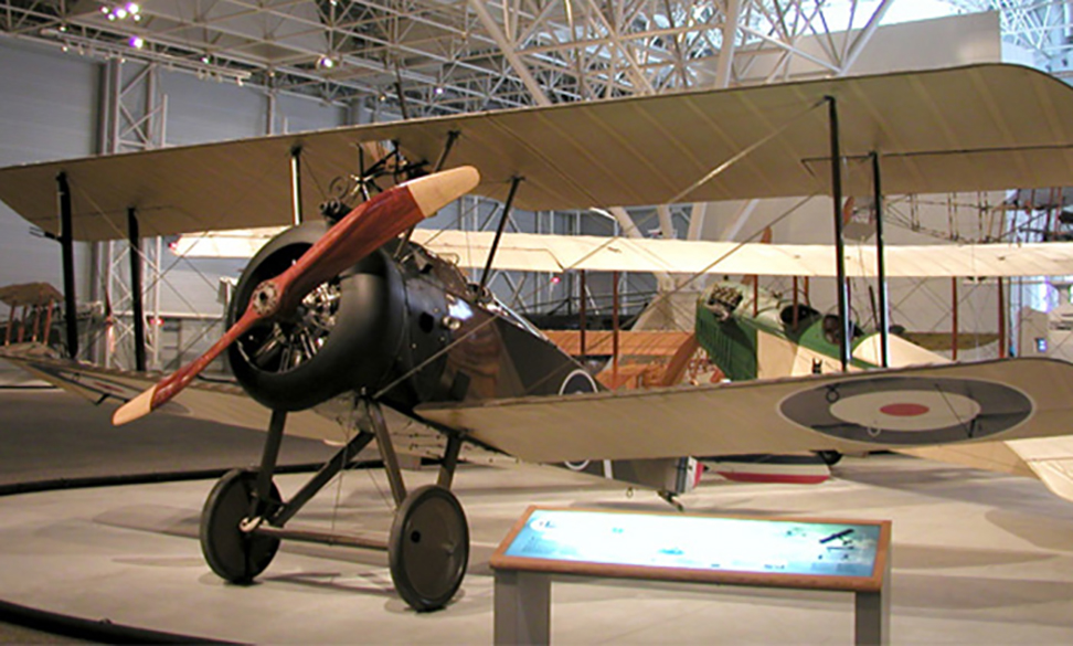 "While there were few photos of the Sopwith 2F.1 Camel performing at the 1967 show, it still occupies a place of honour at the Canada Aviation and Space Museum at Rockcliffe, Ontario. The Sopwith Camel was developed to replace the Sopwith Pup, and began to enter the Royal Flying Corps and the Royal Naval Air Service in the middle of 1917, meeting with immediate success. Although mainly used in Western Europe, Camels also served in Italy. Some Camels were assigned to home defence, with the cockpit positioned further back and guns placed on the upper wings. The 2F.1 Camel was produced for the Royal Naval Air Service with more powerful engines and modified armament. A total of 5,490 Camels were built. The name ""Camel"" was derived from the hump-shaped cover over the machine guns. In order to combat Zeppelins, Camels were flown from barges towed behind destroyers, from platforms on the gun turrets of larger ships, and from early aircraft carriers. A Camel successfully flew after being dropped from an airship, an experiment testing an airship's ability to carry its own defensive aircraft. An armoured trench-fighting version was flown, but did not go into production. PHOTO/TEXT: Canada Aviation and Space Museum"
