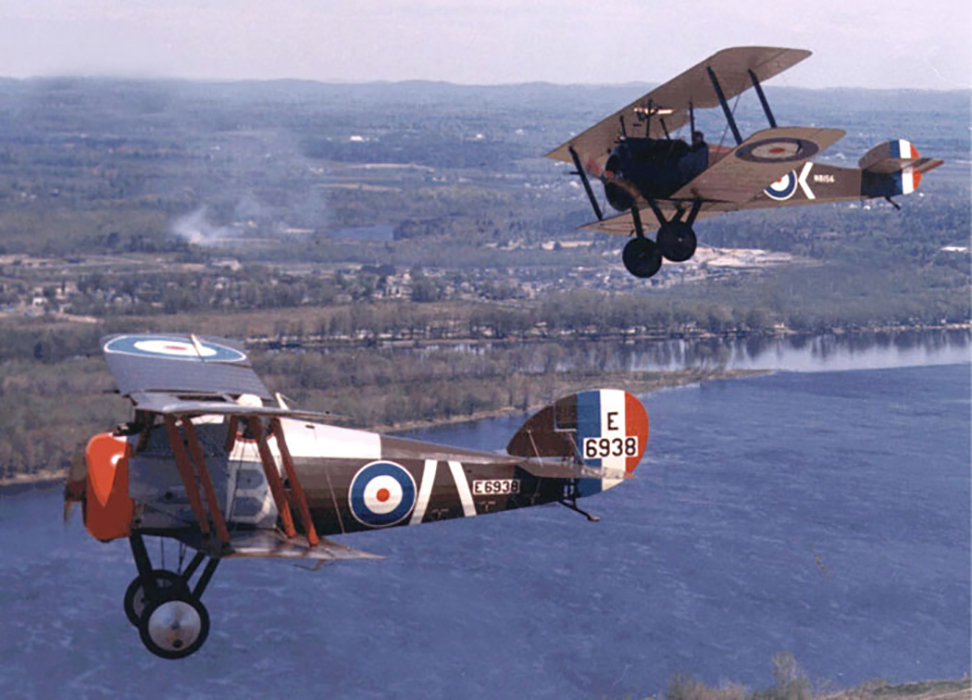 Two vintage bi-planes bearing RCAF rondels fly over water, with land in the background.