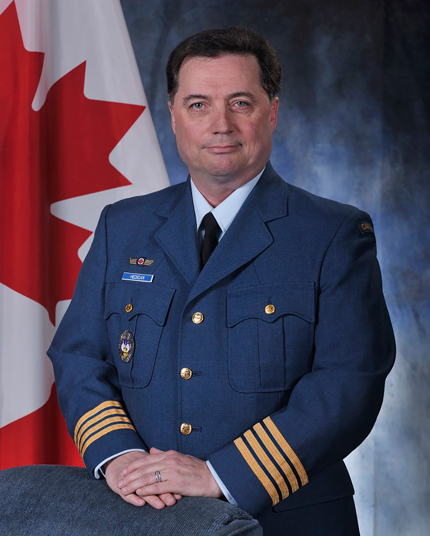 A man in a blue uniform stands beside a Canadian flag with his hands resting on the back of a chair, and looks at the camera.