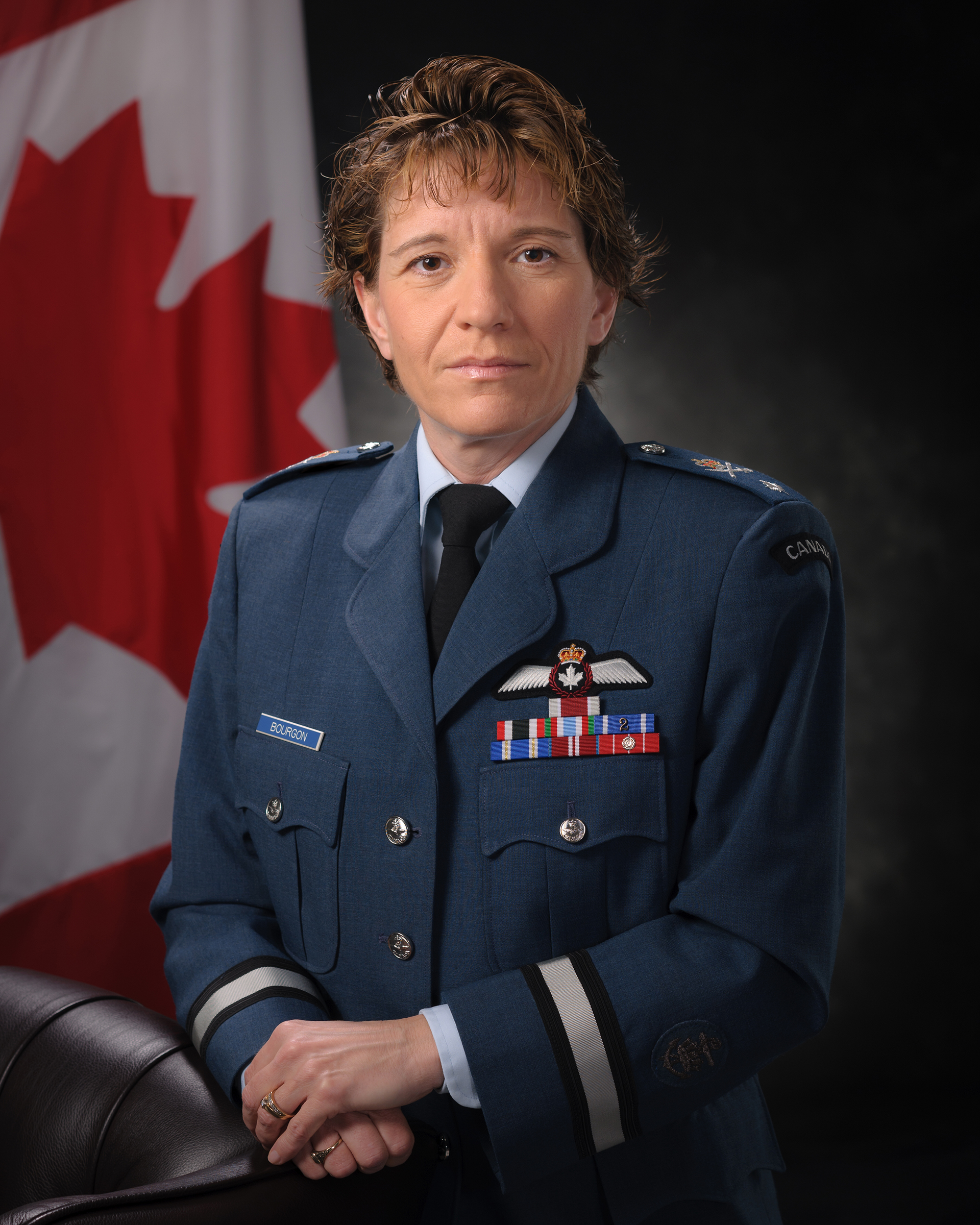 A three-quarters portrait photo of a woman in a blue military uniform standing with her hands folded on the back of a chair.